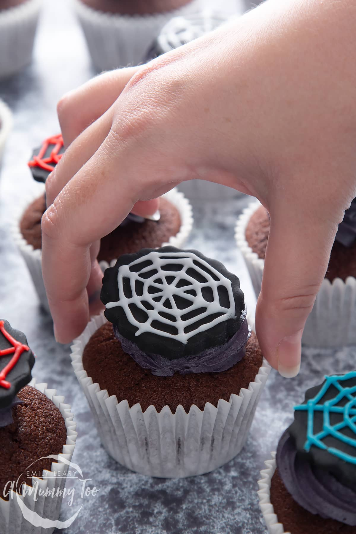 Spider web cupcakes arranged on a black surface. The chocolate sponge cupcakes are topped with purple vanilla buttercream and discs of black sugar paste decorated with spider web icing. A hand reaches to take one.