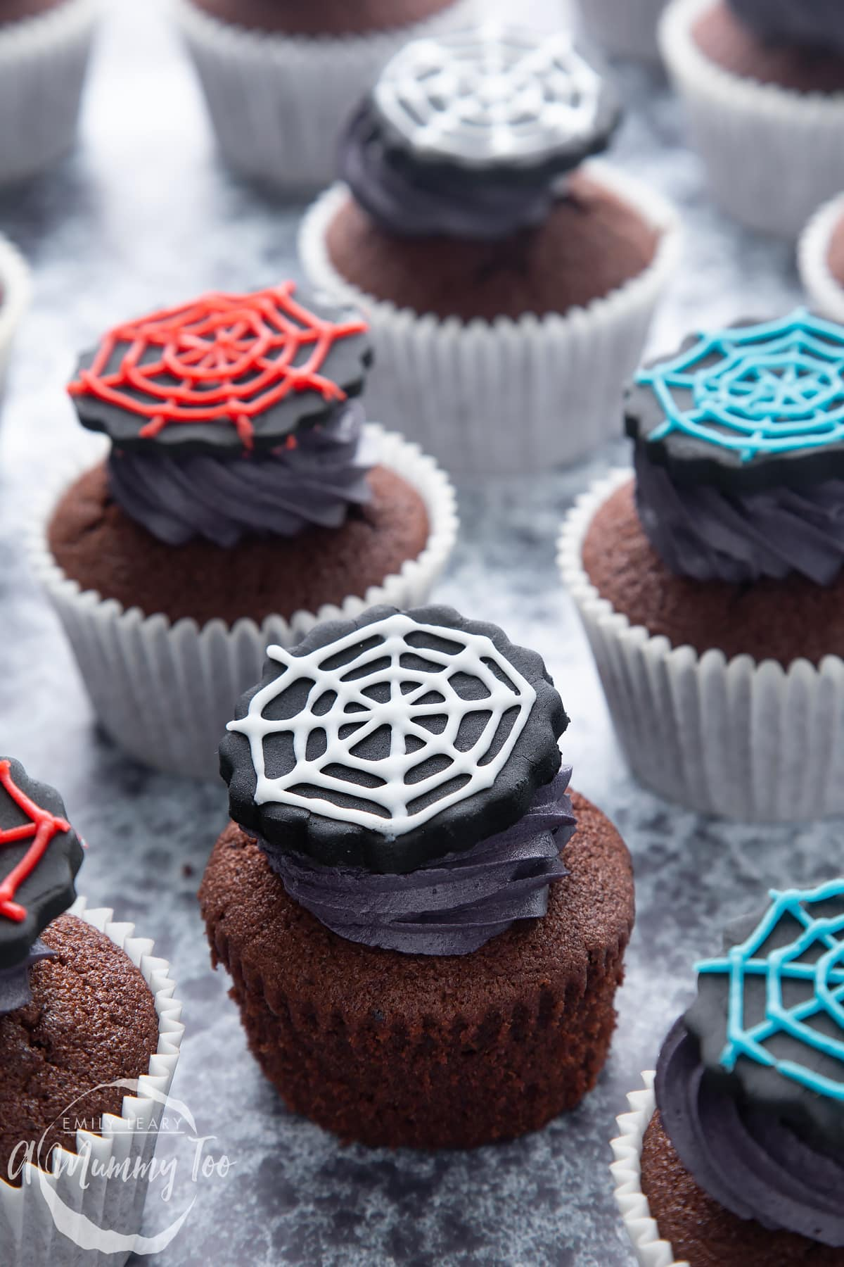 Spider web cupcakes arranged on a black surface. The chocolate sponge cupcakes are topped with purple vanilla buttercream and discs of black sugar paste decorated with spider web icing.