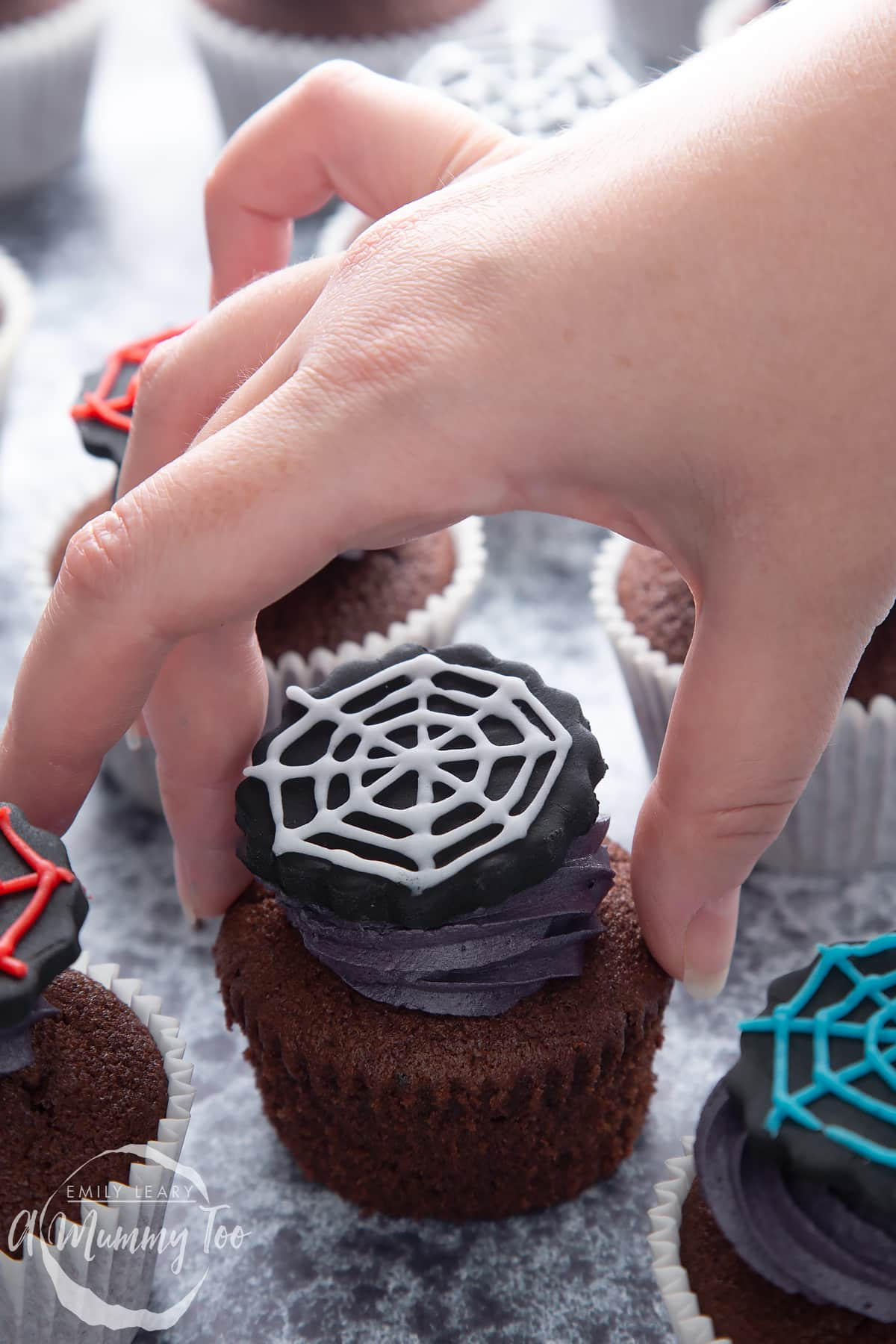 Spider web cupcakes arranged on a black surface. The chocolate sponge cupcakes are topped with purple vanilla buttercream and discs of black sugar paste decorated with spider web icing. A hand reaches to take an unwrapped one.