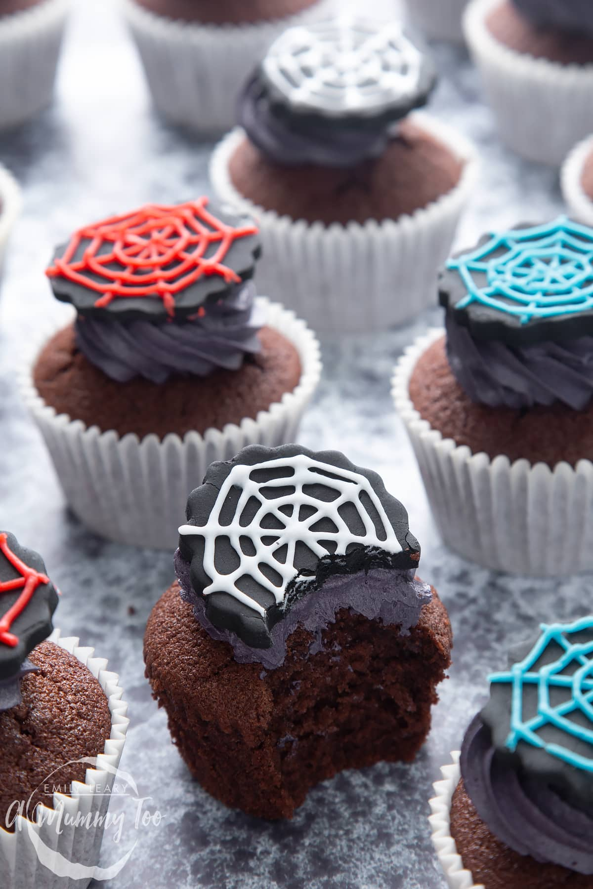 Spider web cupcakes arranged on a black surface. The chocolate sponge cupcakes are topped with purple vanilla buttercream and discs of black sugar paste decorated with spider web icing. One cupcake has been bitten.
