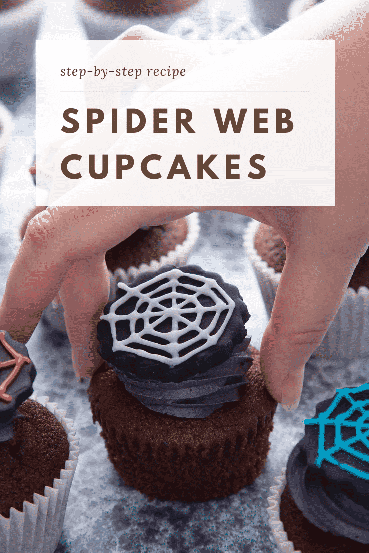 Spider web cupcakes arranged on a black surface. The chocolate sponge cupcakes are topped with purple vanilla buttercream and discs of black sugar paste decorated with spider web icing. A hand reaches for one. Caption reads: Step-by-step recipe spider web cupcakes
