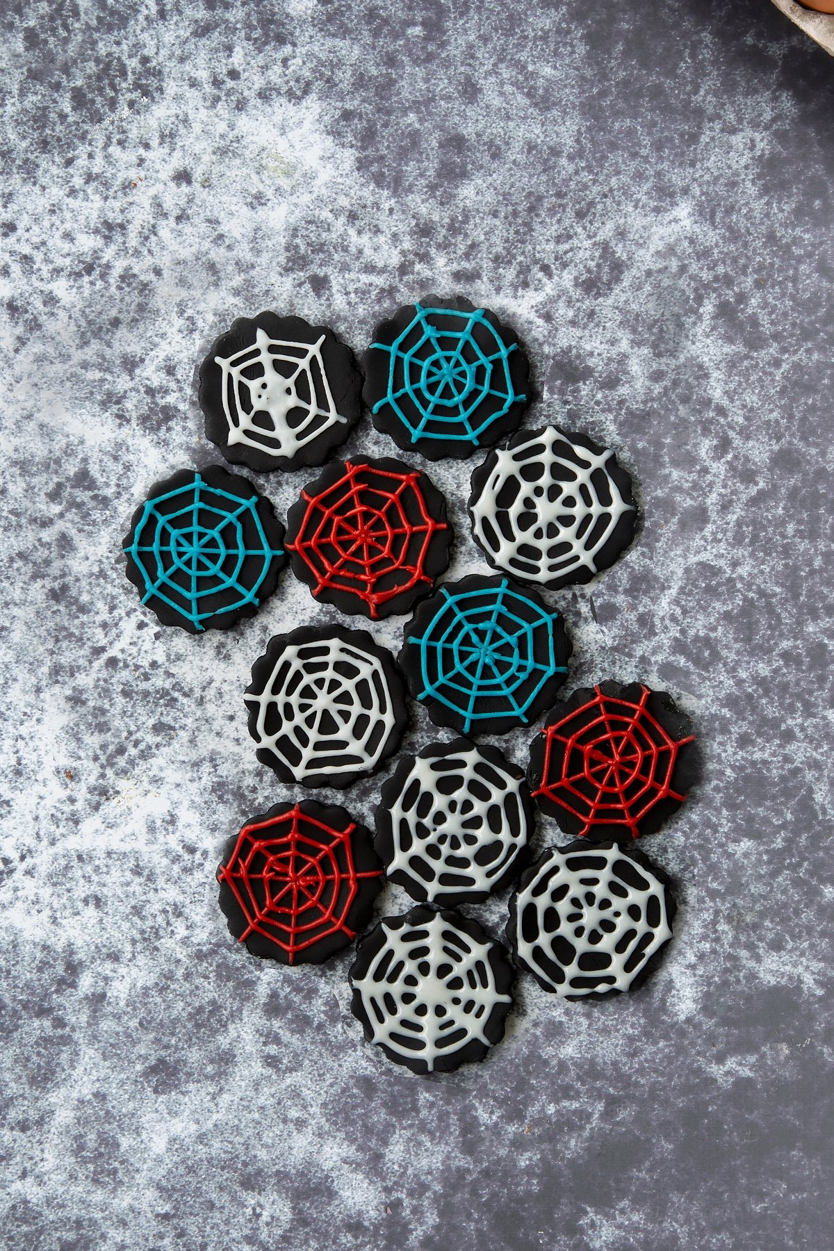 Discs of black sugar paste on a dark background. The discs have been decorated with spider webs using red, blue and white icing pens.