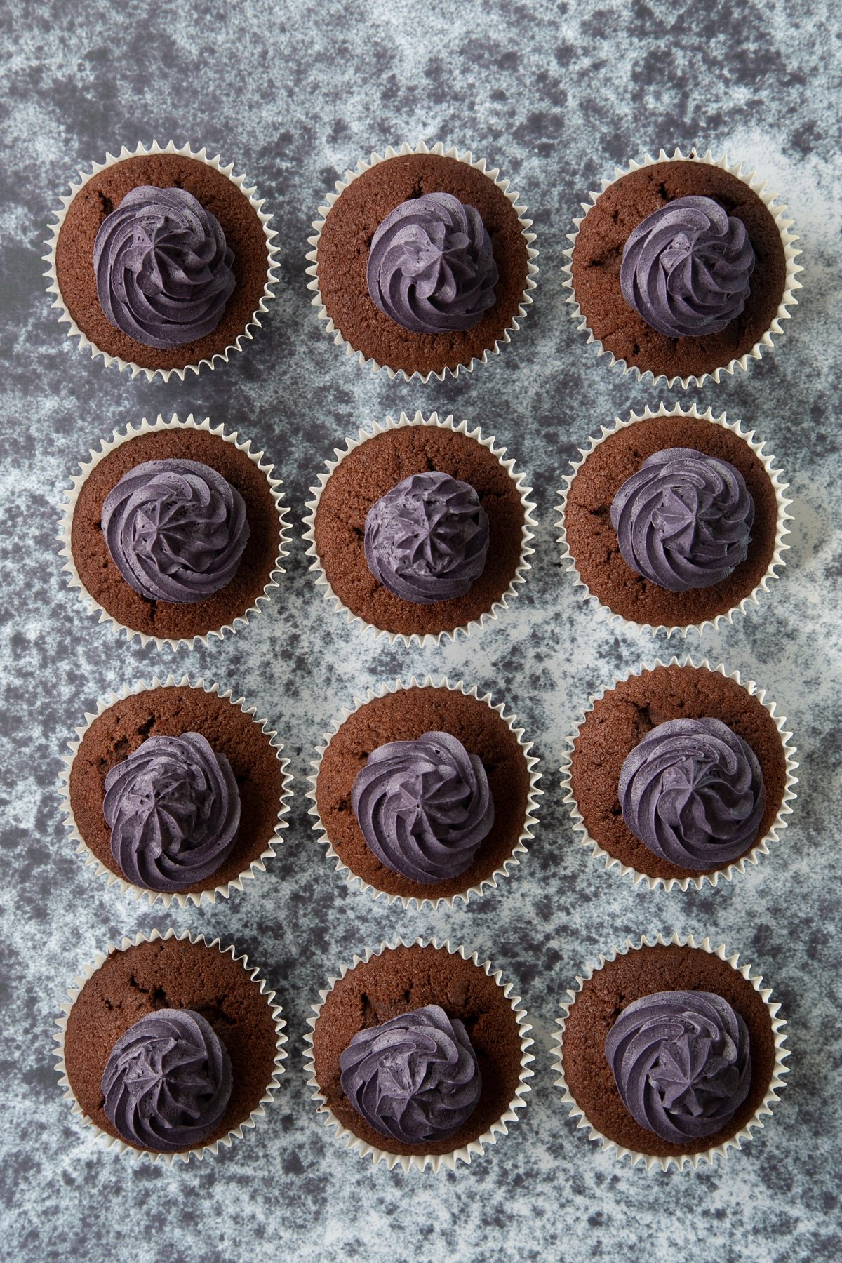 12 chocolate cupcakes with purple frosting on a dark background, shown from above.