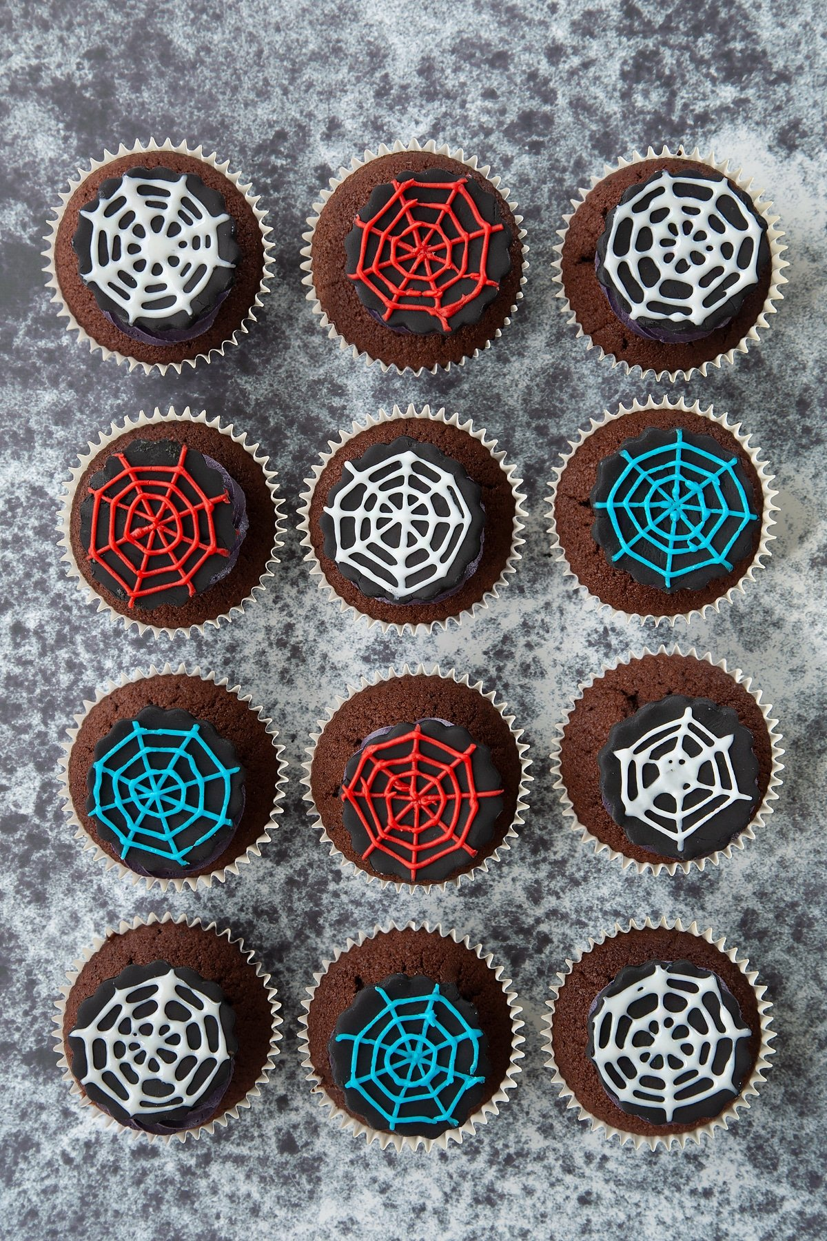 Spider web cupcakes arranged on a black surface, shown from above. The chocolate sponge cupcakes are topped with purple vanilla buttercream and discs of black sugar paste decorated with spider web icing.