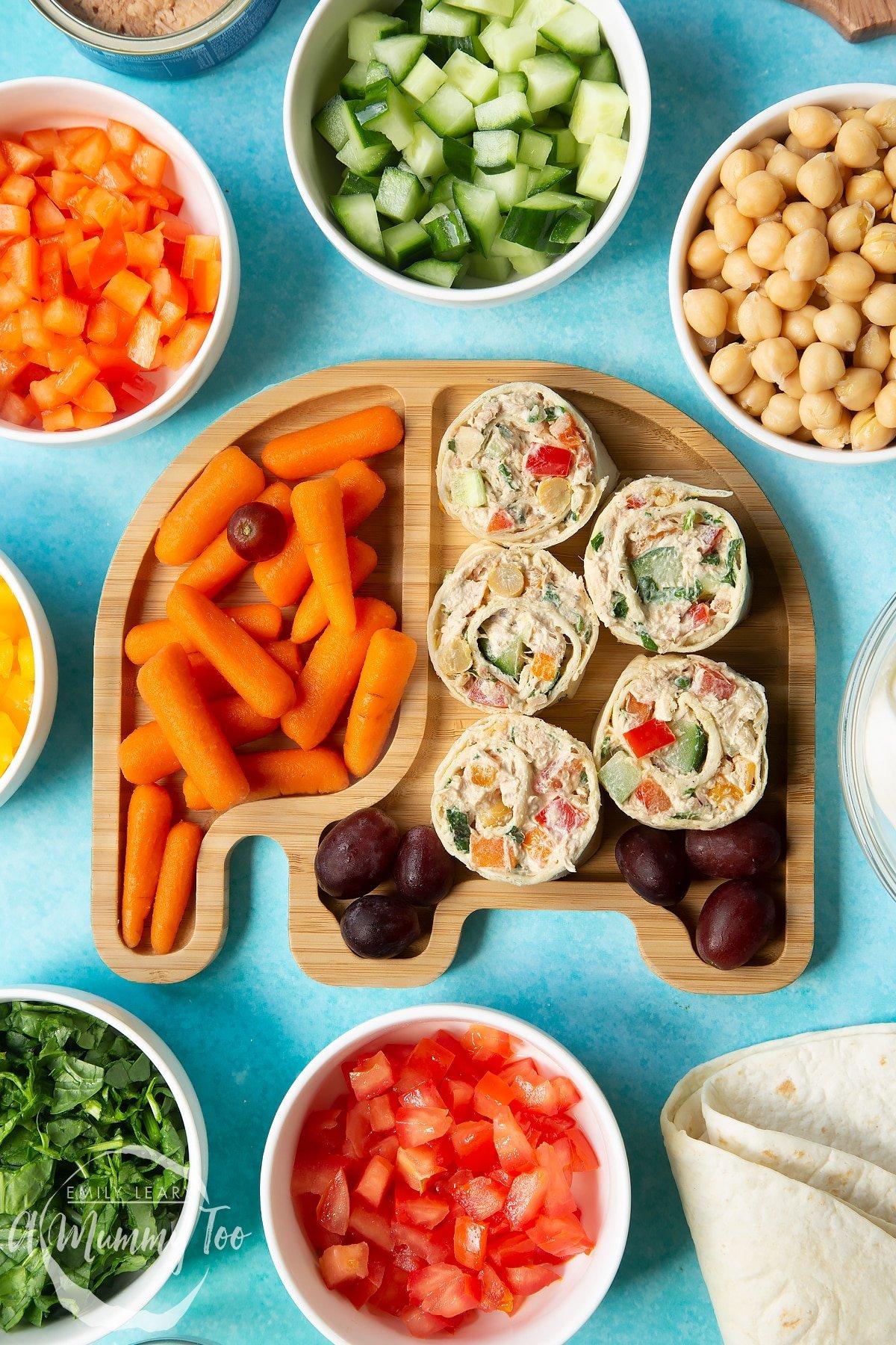 Tuna pinwheels served on a bamboo plate shaped like an elephant with fresh fruit and veg.