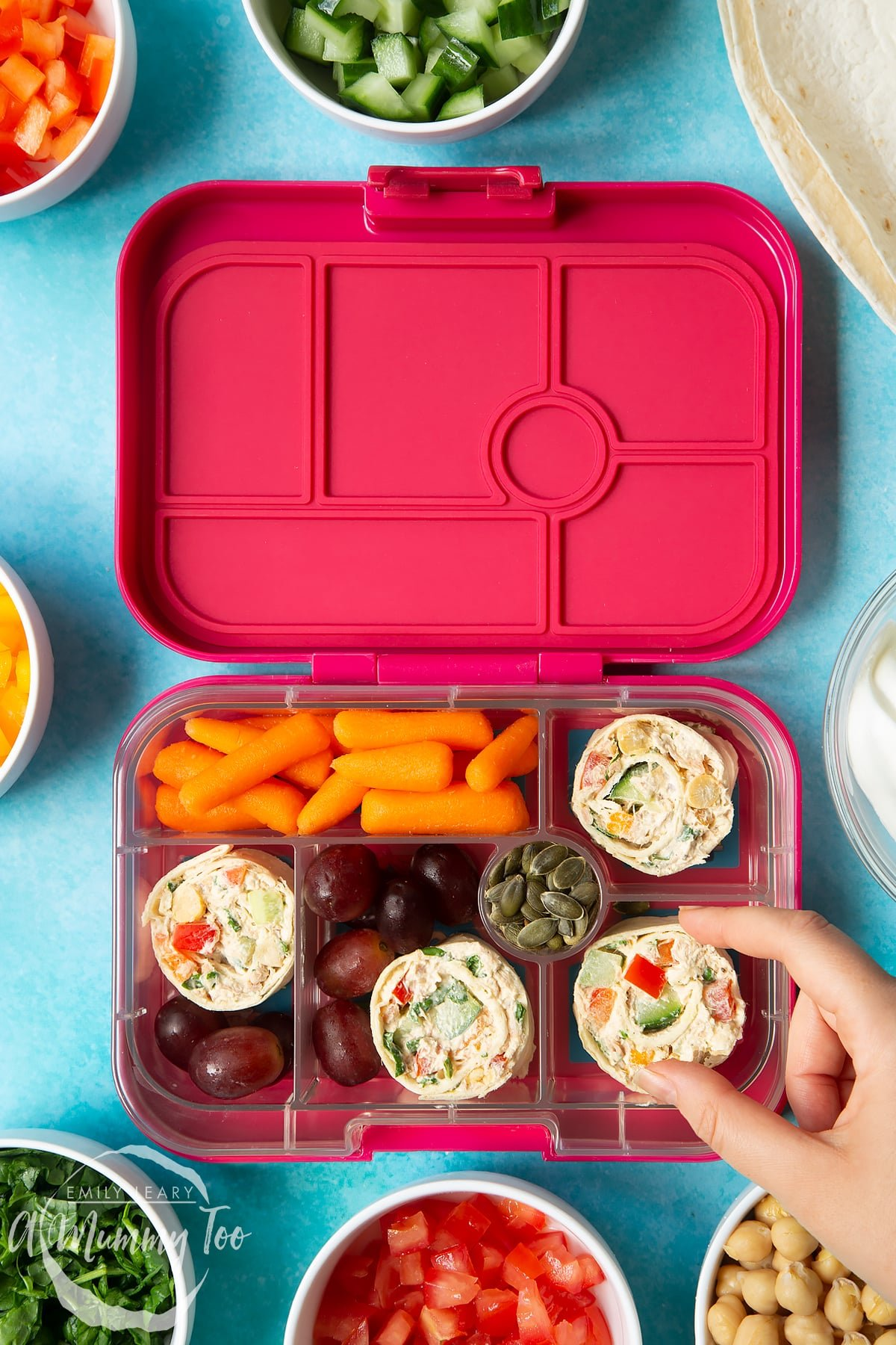 Tuna pinwheels in a lunchbox with fresh fruit and veg. A hand reaches to take a pinwheel.