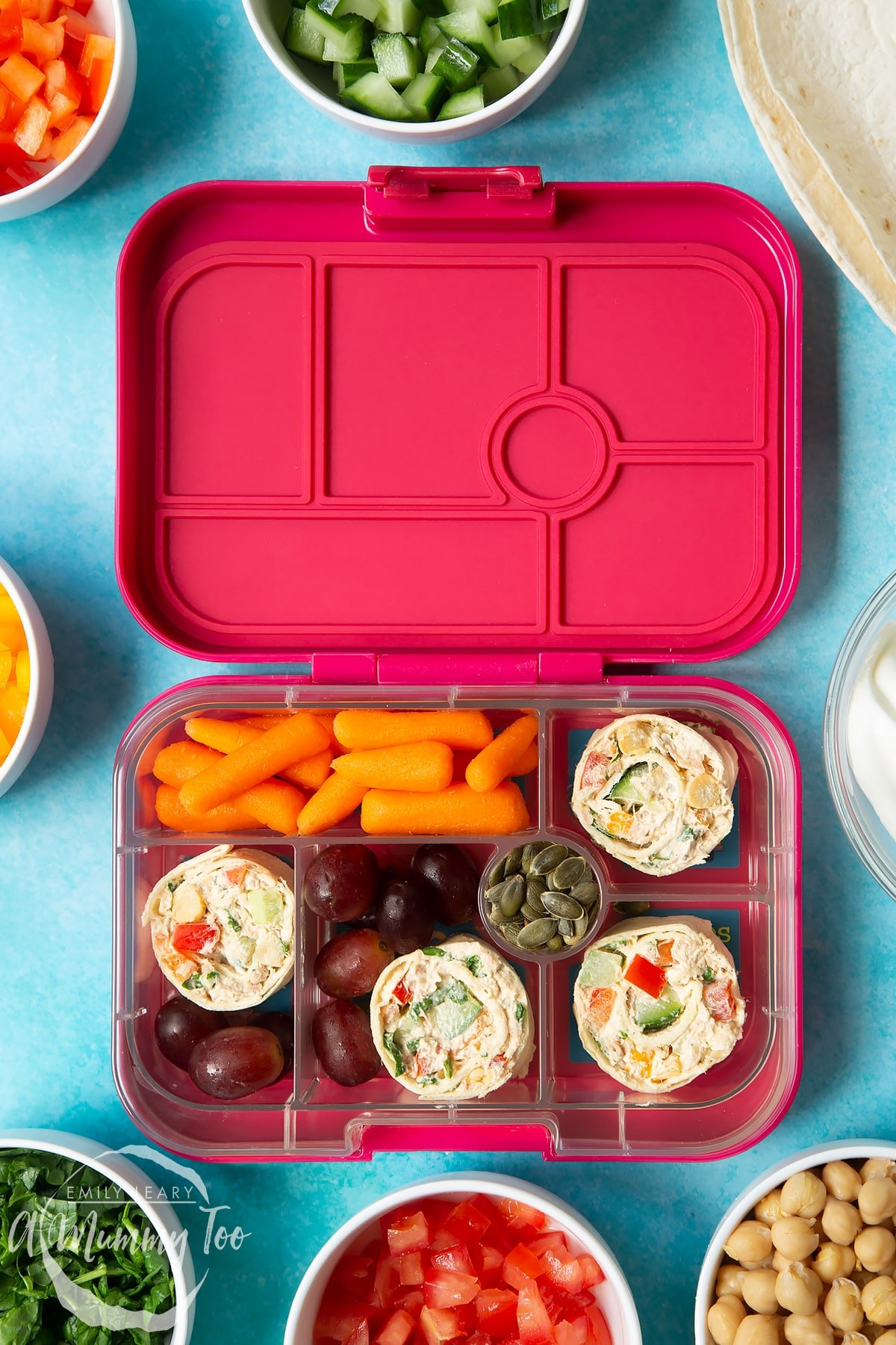Tuna pinwheels in a lunchbox with fresh fruit and veg.