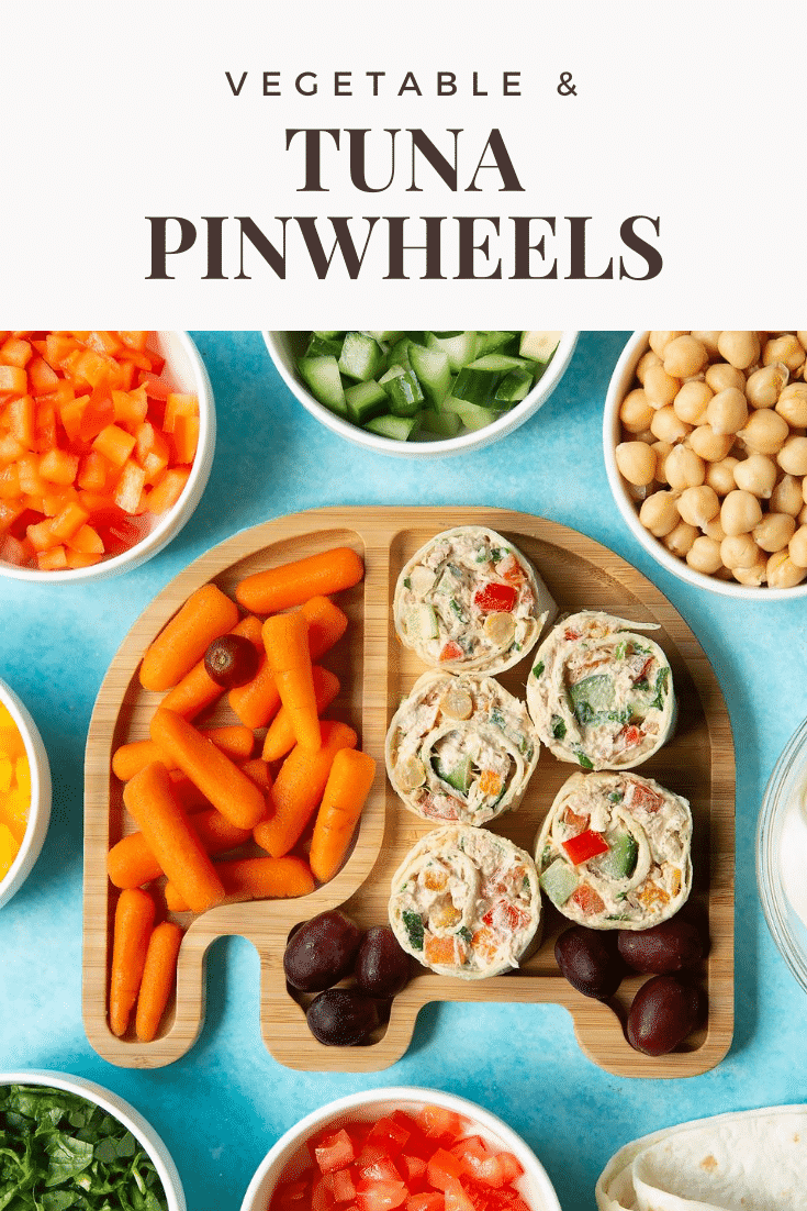 Tuna pinwheels on a bamboo elephant plate with fresh fruit and veg. Caption reads: Vegetable & tuna pinwheels.
