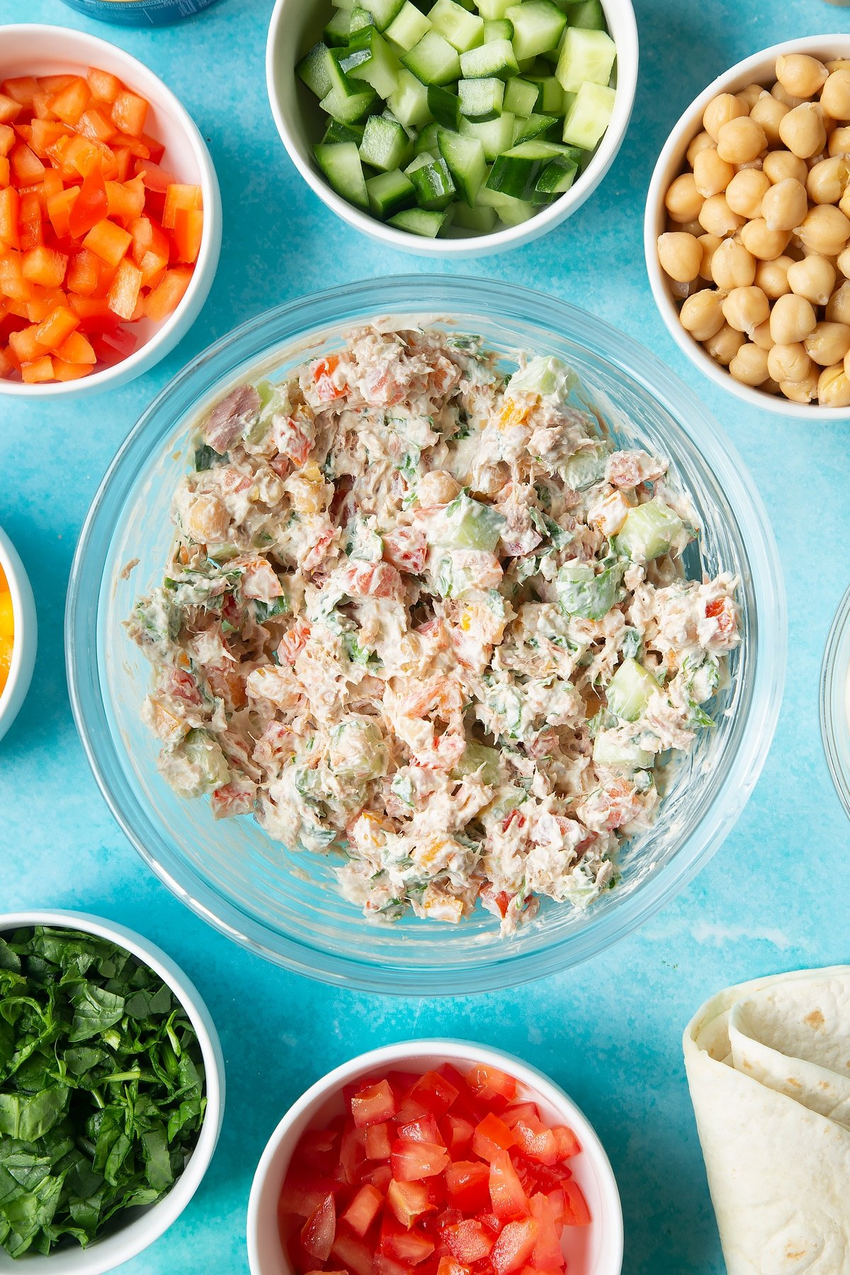 A mix of cream cheese, tuna and veg in a bowl. Ingredients to make tuna pinwheels surround the bowl.
