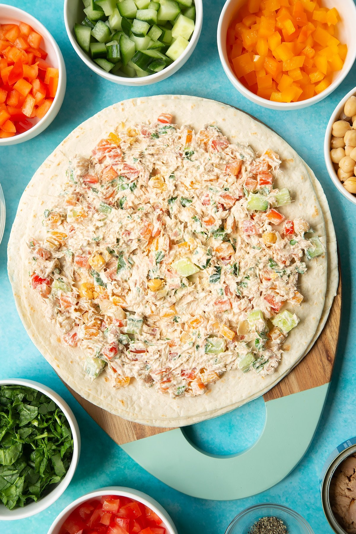Flour tortillas spread with a mix of cream cheese, tuna and veg. Ingredients to make tuna pinwheels surround the board.