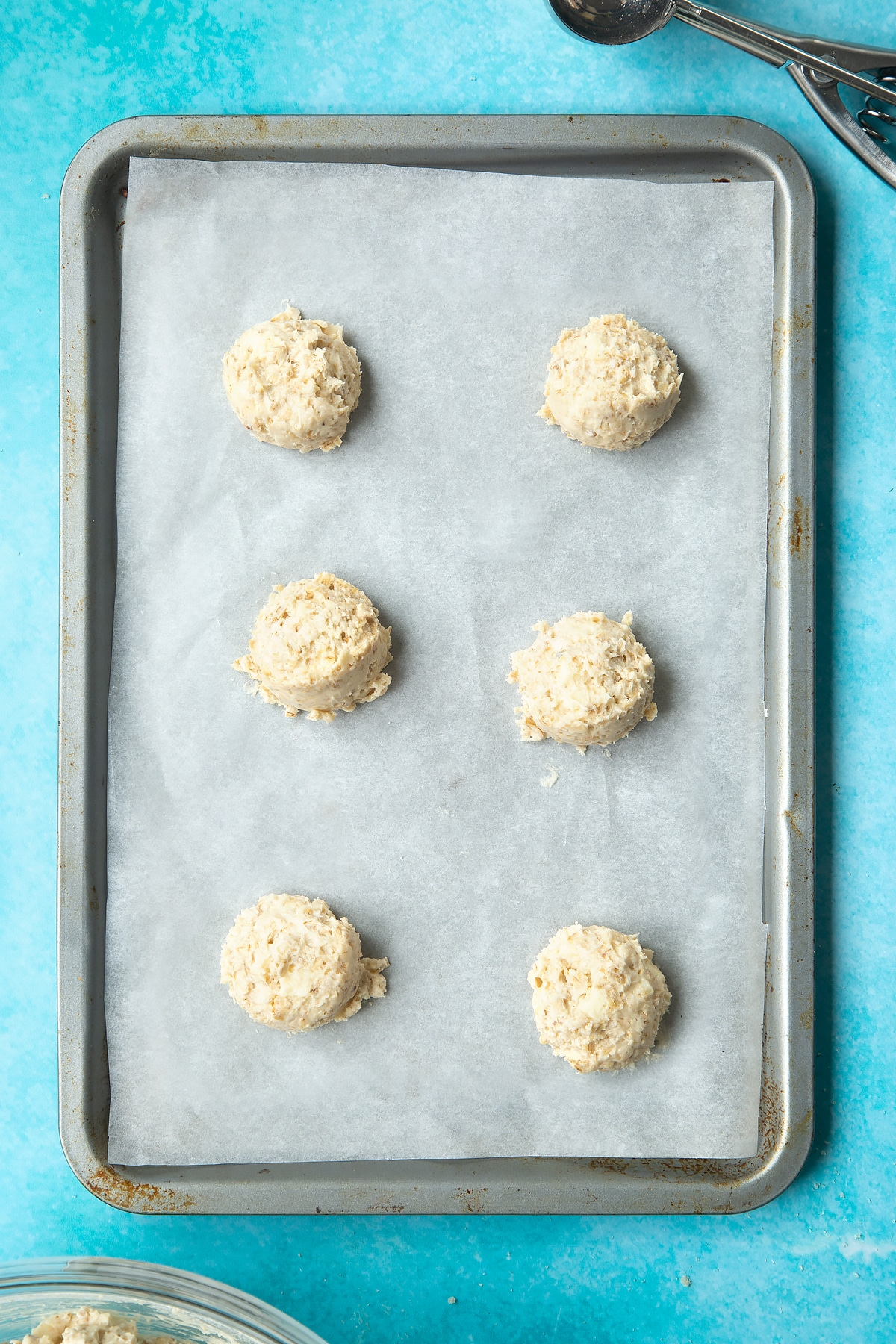 Overhead shot of white chocolate chip oatmeal cookie dough balls on a lined baking tray