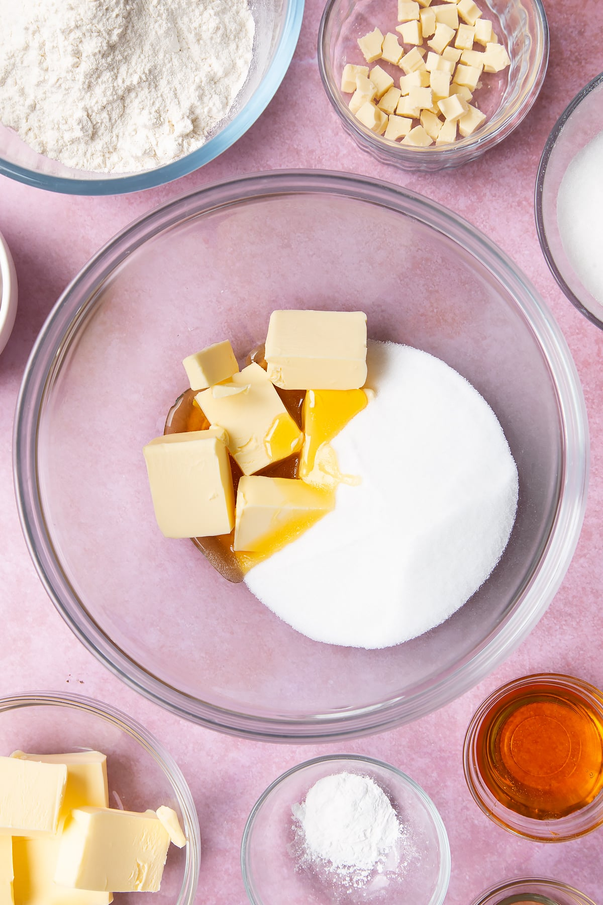 Overhead shot of butter, golden syrup and sugar in a large clear bowl