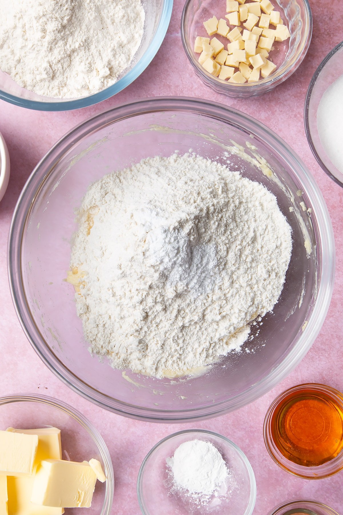 Overhead shot of flour on top of butter mix and an egg  in a large mixing bowl