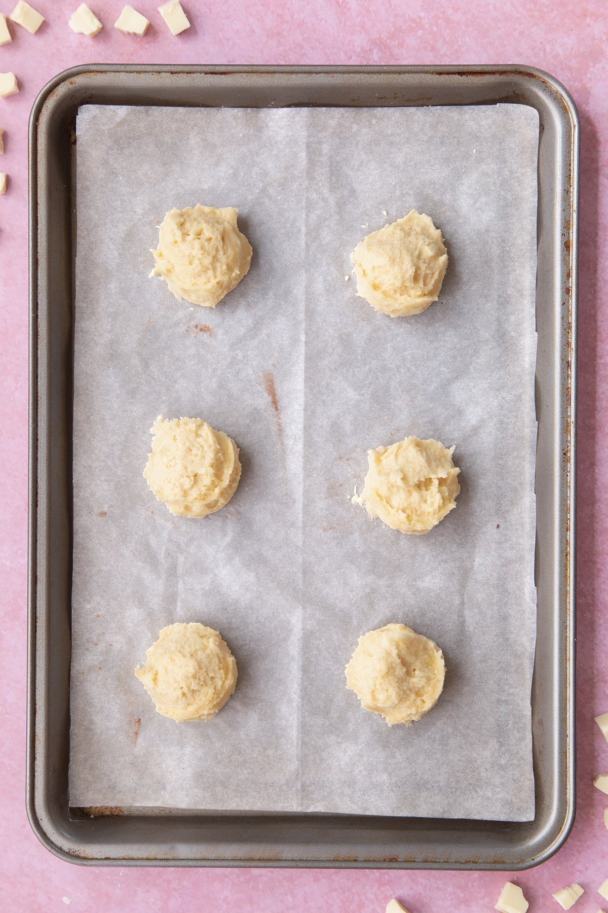 Overhead shot of cookie dough in balls on a baking sheet.