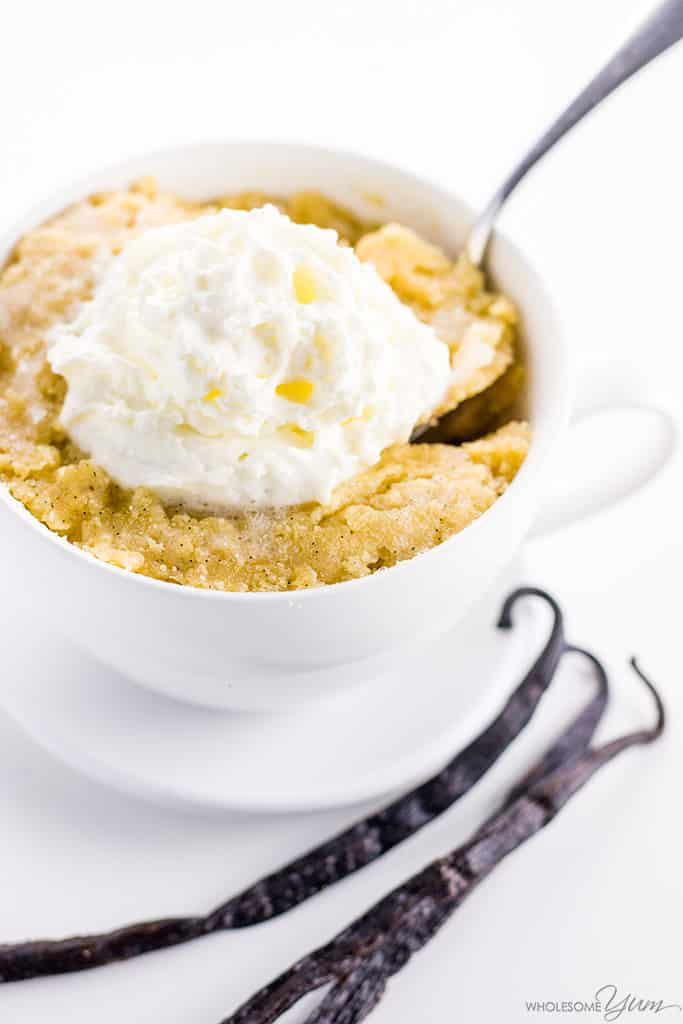Keto paleo vanilla mug cake, topped with cream. A spoon delves into the cake. Two vanilla pods sit to the side of the mug.