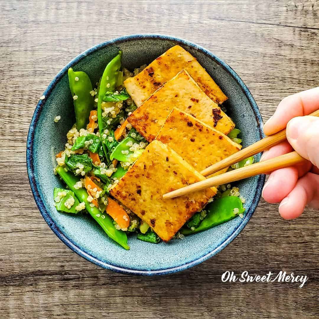 Slices of tofu in a decorative bowl with garlic, ginger, slices of lime, quinoa and green beans. A hand reaches in with a pair of chopsticks to pick a slice of the tofu up.