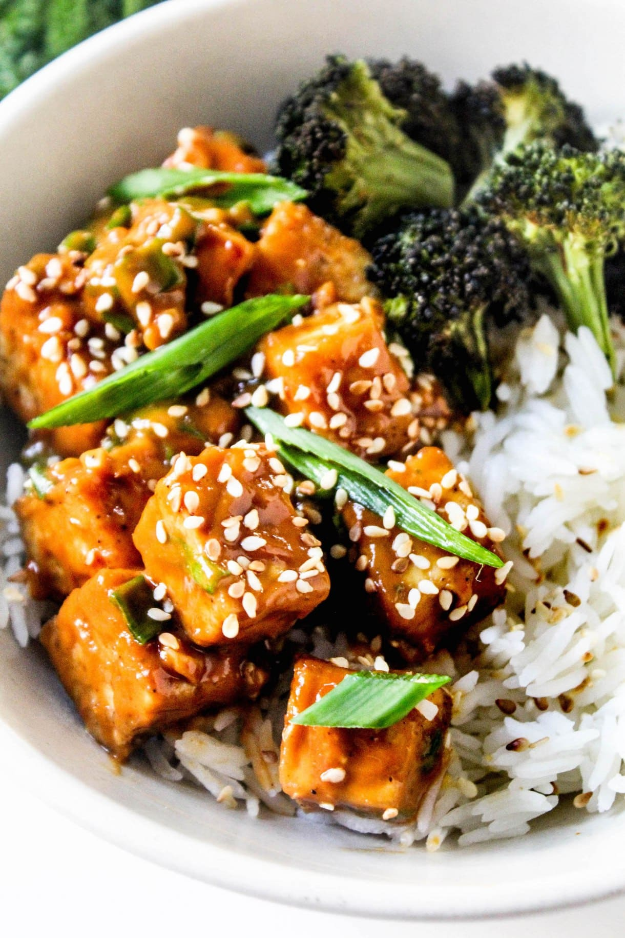 Peanut sauce tofu cubes sit on a bowl of white rice with a side of broccoli inside a white bowl.