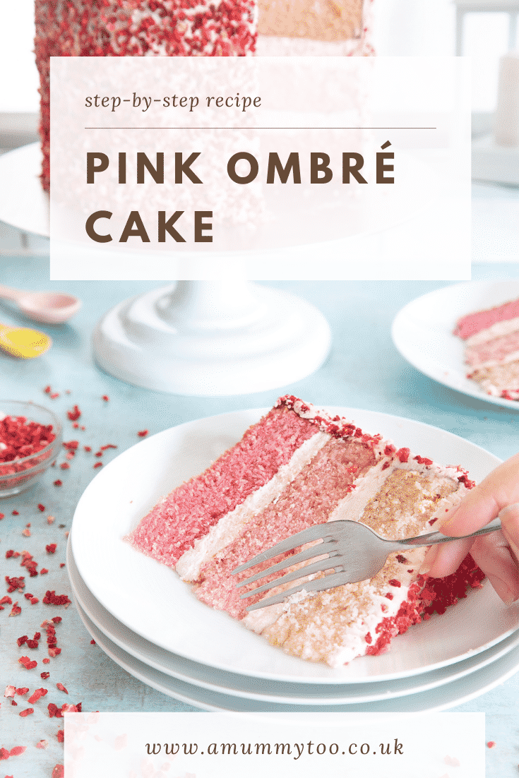 A slice of pink ombre cake on a stack of small white plates. The cake has three layers, each an increasingly intense shade of pink. The sponges are layered with pale pink frosting and the outside is decorated with freeze dried strawberry pieces. A hand holds a fork which is delving into the cake slice. Caption reads: Step-by-step recipe pink ombre cake