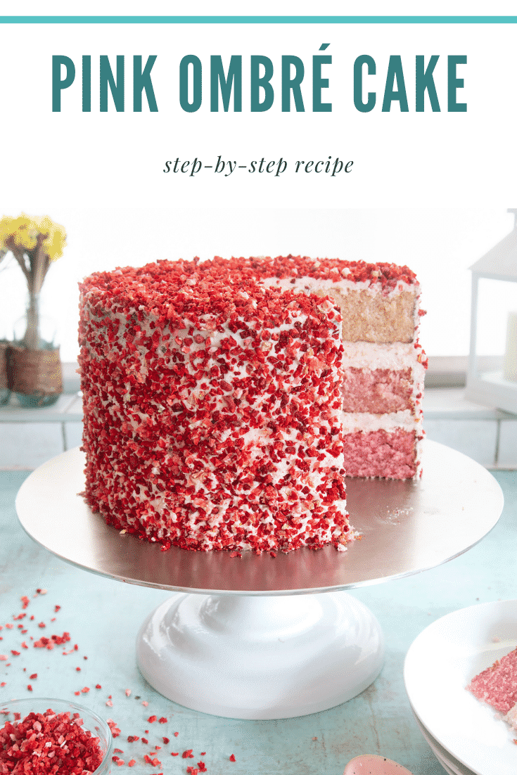 A pink ombre cake on a cake stand. The cake has three layers, each an increasingly intense shade of pink. The sponges are layered with pale pink frosting and the outside is decorated with freeze dried strawberry pieces. Caption reads: pink ombre cake step-by-step recipe