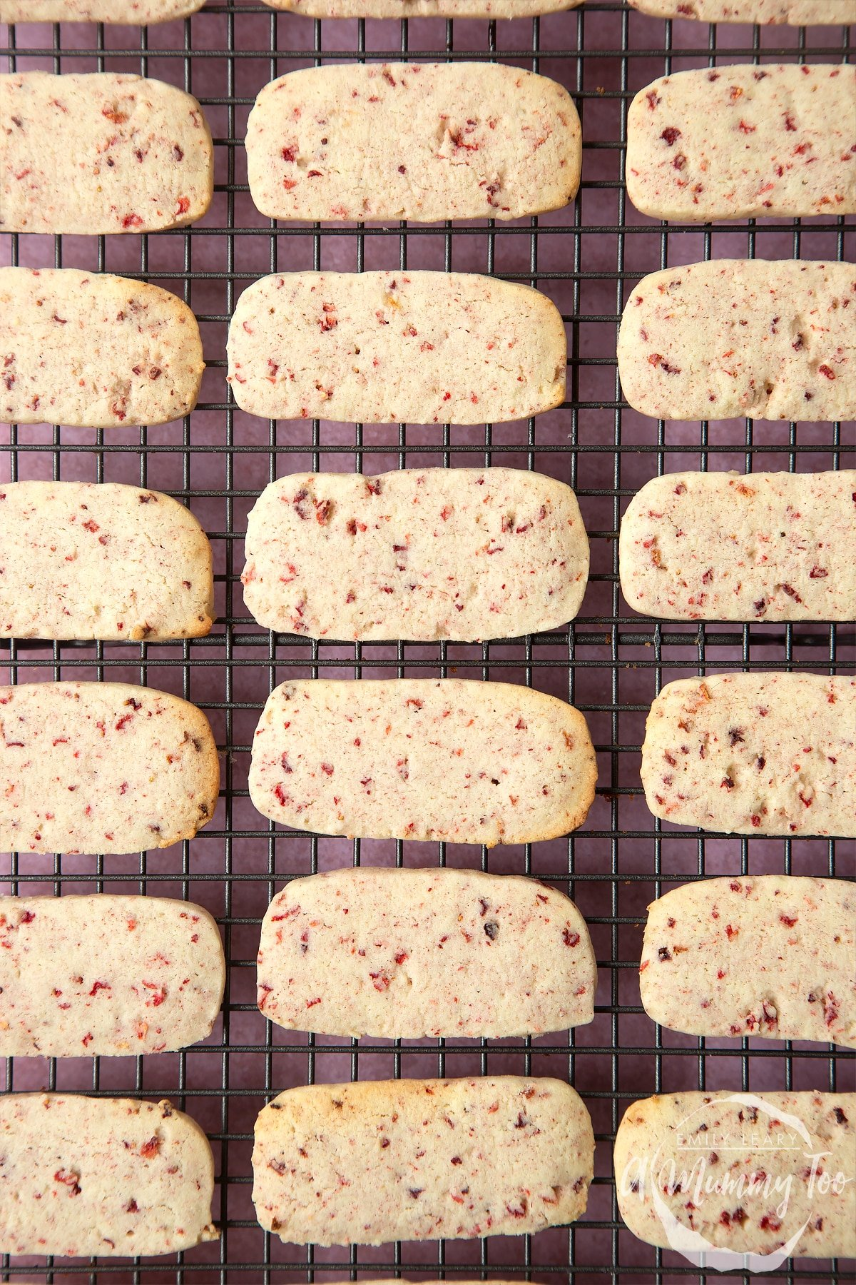 Strawberry biscuits lined up in rows on a cooling rack.