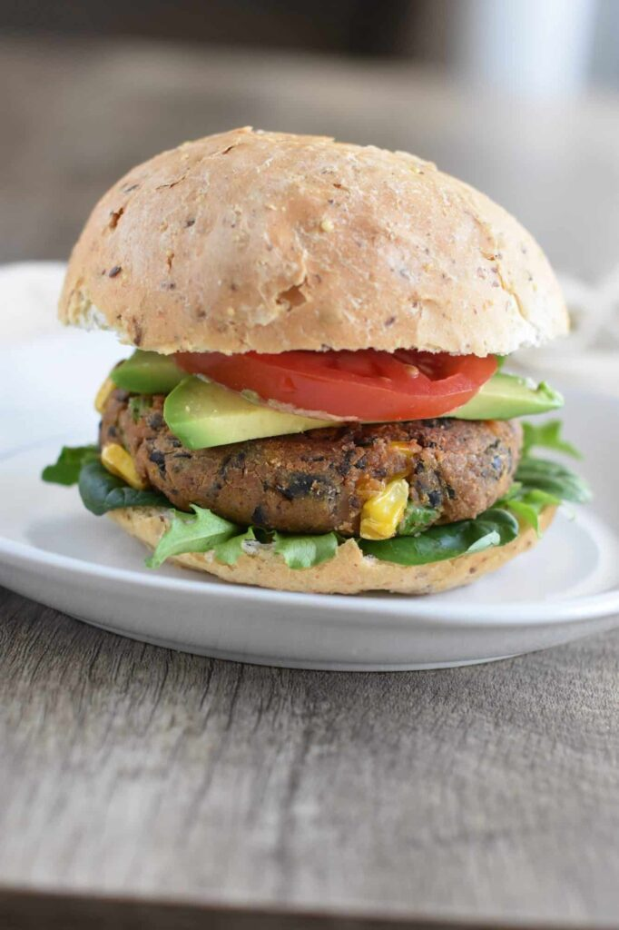 Sweet Potato Black Bean Burgers with avocado, tomato and lettuace sat on a plain white plate on a wooden table top.