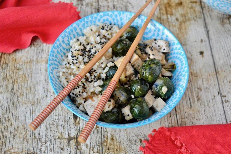 Teriyaki rice sits inside a blue decorative bowl on a wooden background. A pair of chopsticks lay across the top of the bowl.