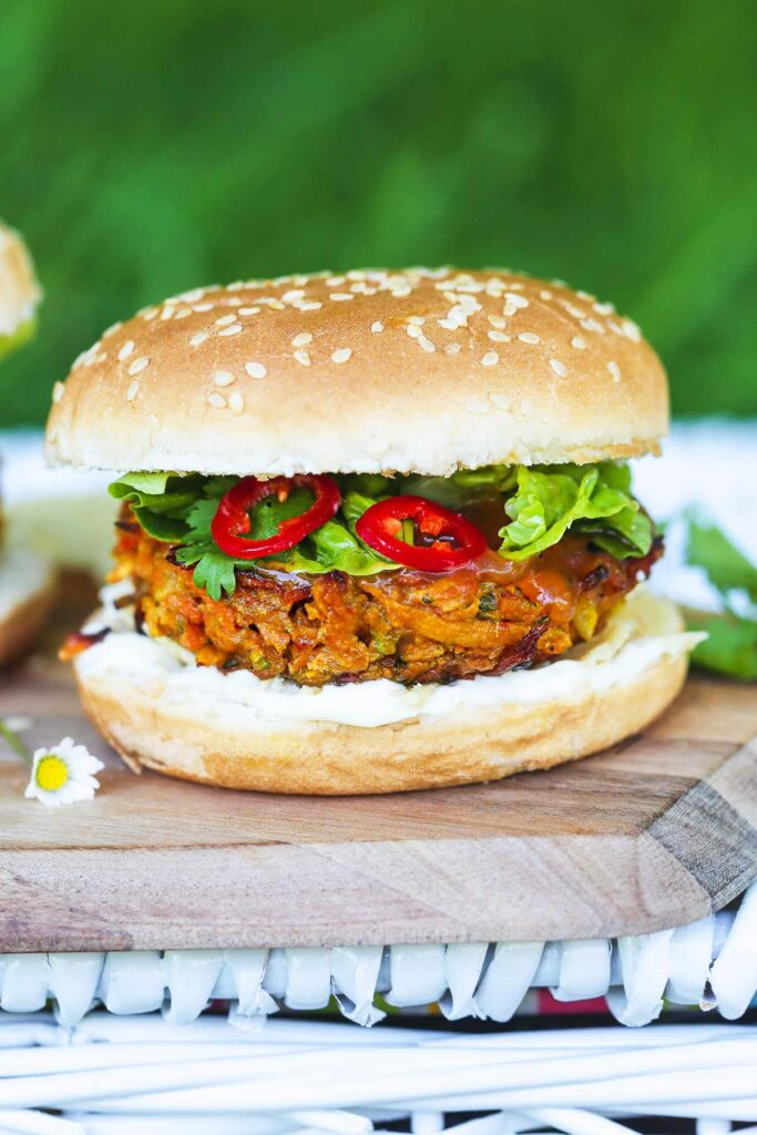 A Vegan Bhaji Burger sat on a wooden surface with chili peppers on show.