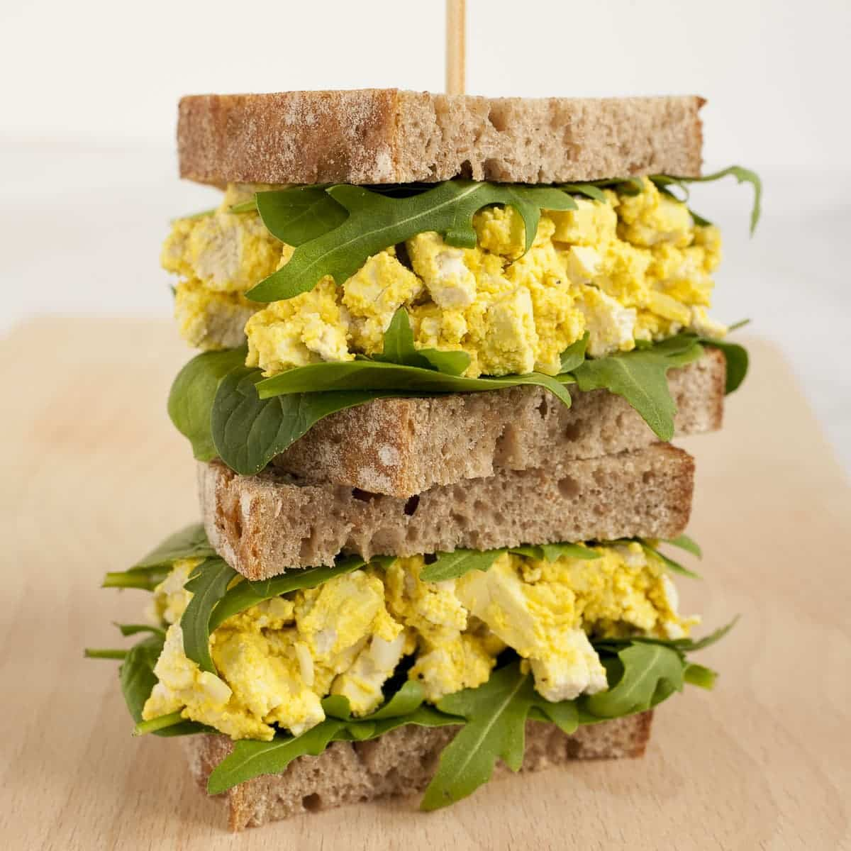 Vegan egg sandwiches stacked on top of one and other with a skewer through the top to keep them in place.