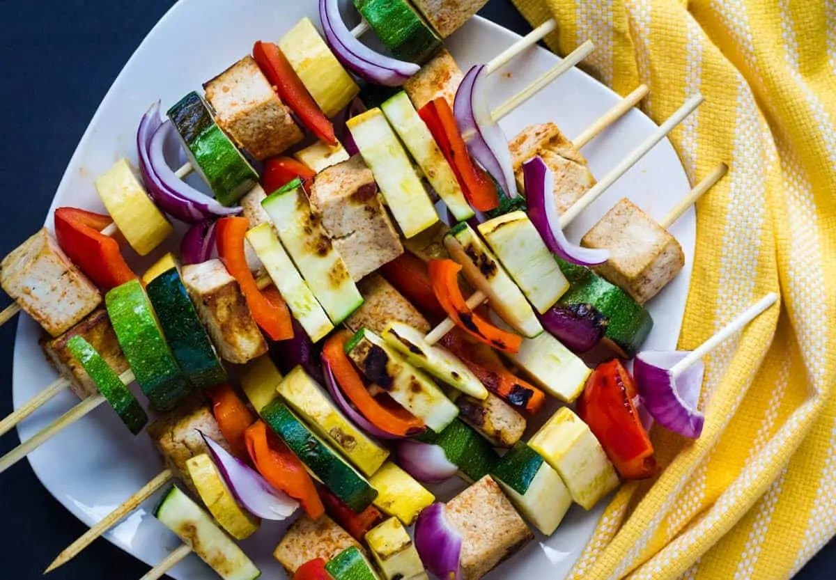 Kebab skewers made with tofy and vegetables stacked torgher on a white plate.