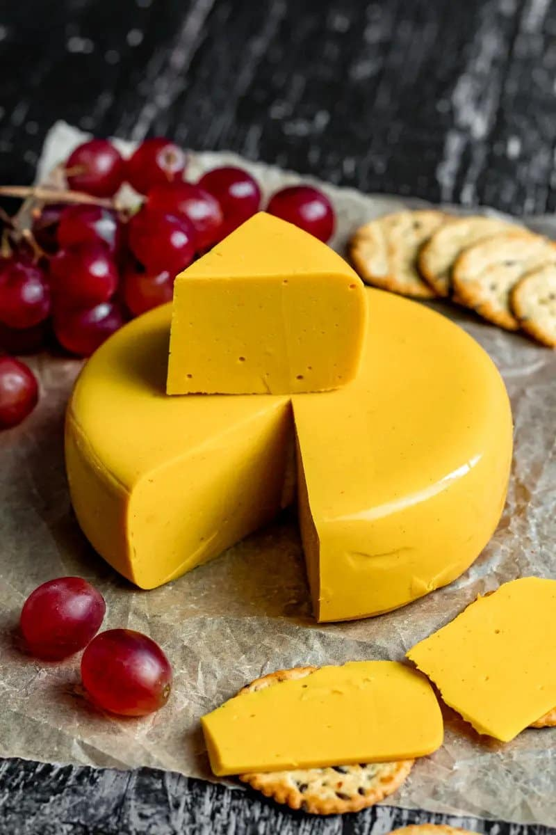 A round block of vegan cheddar cheese which has had a slice cut out. Grapes and a slice of cheese on a cracker sit in the foreground.