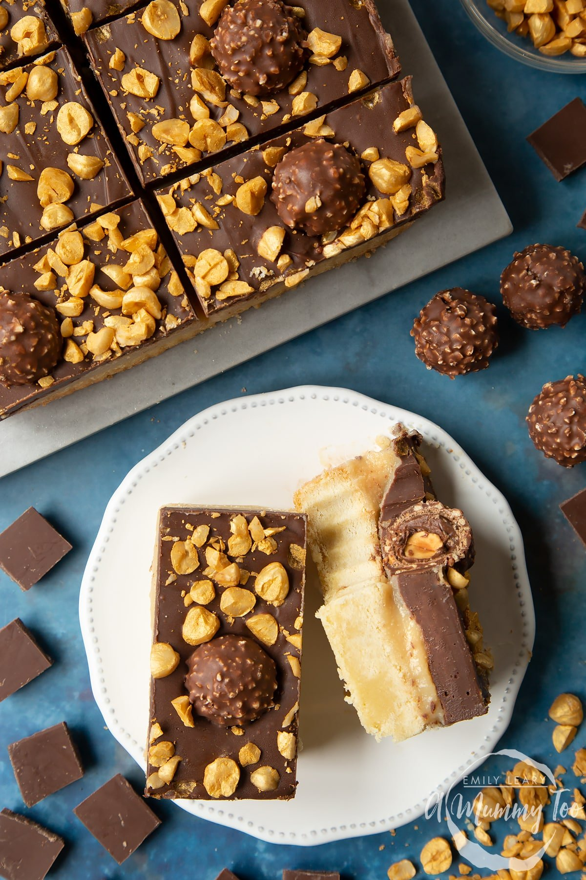 Two Ferrero Rocher slices on a plate. One is turned on its side and has a bite out of it. To the side is a tray with more slices.
