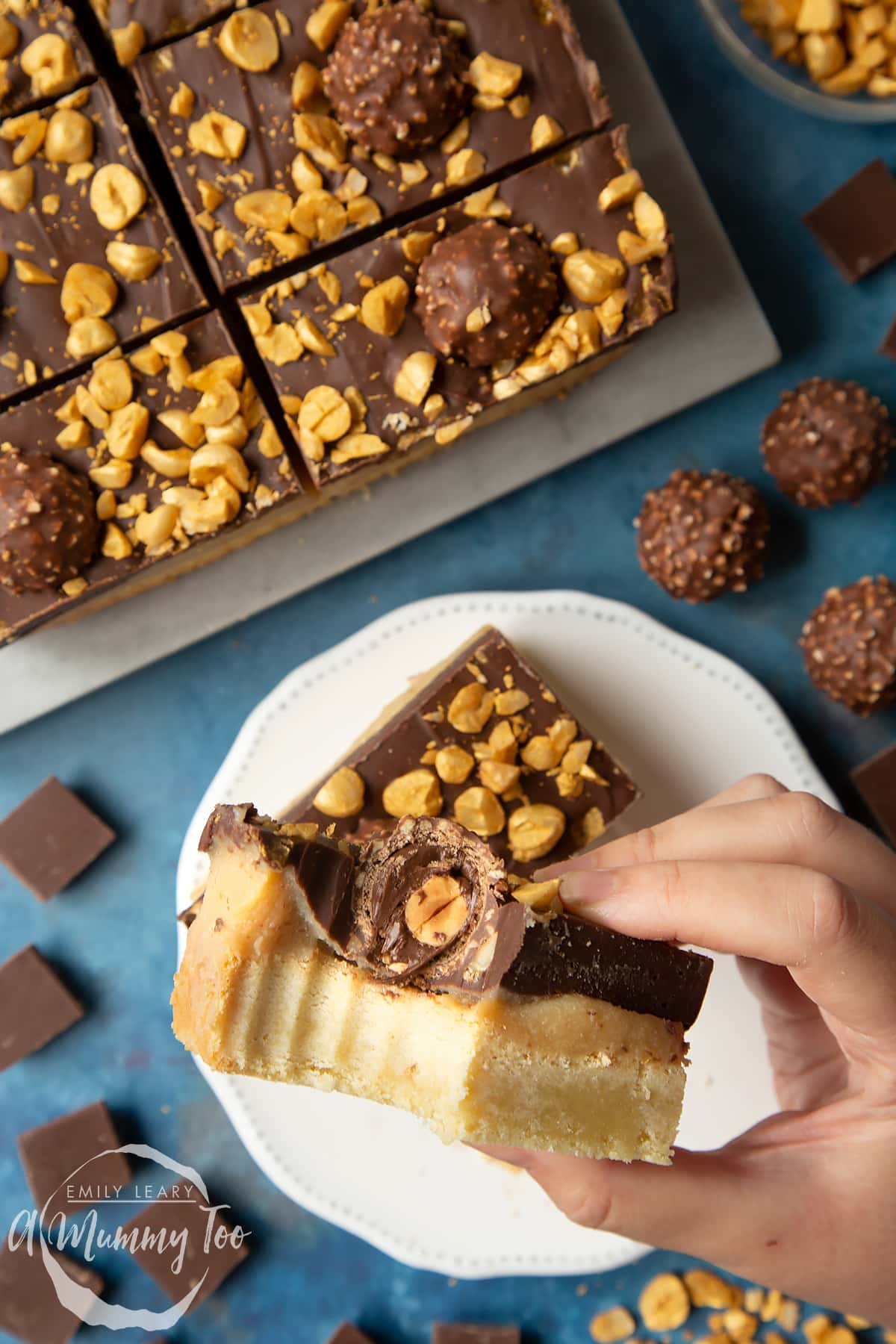 Hand holding a Ferrero Rocher slice with a bite out of it. Below is a plate and tray with more slices.