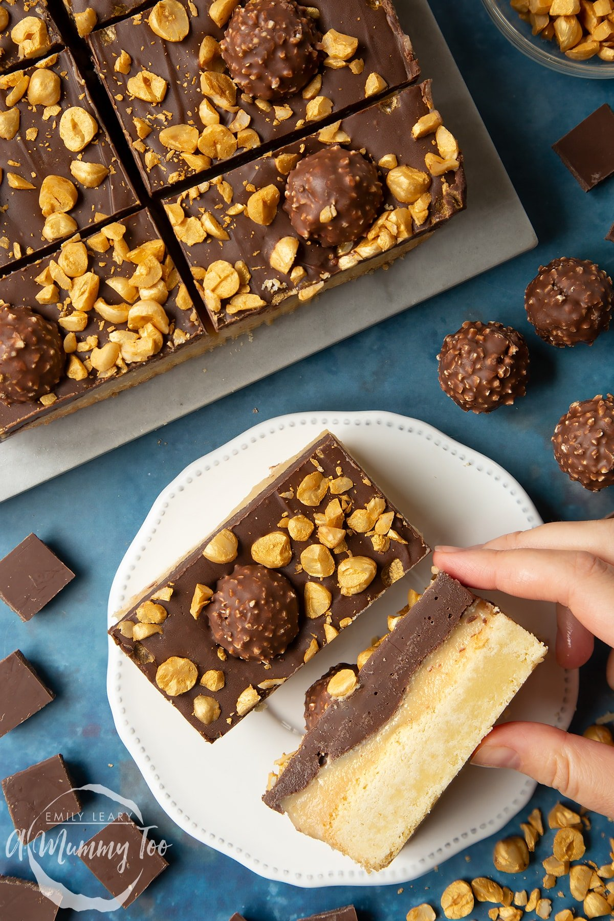 Two Ferrero Rocher slices on a plate. One is turned on its side - a hand reaches for it. To the side is a tray with more slices.