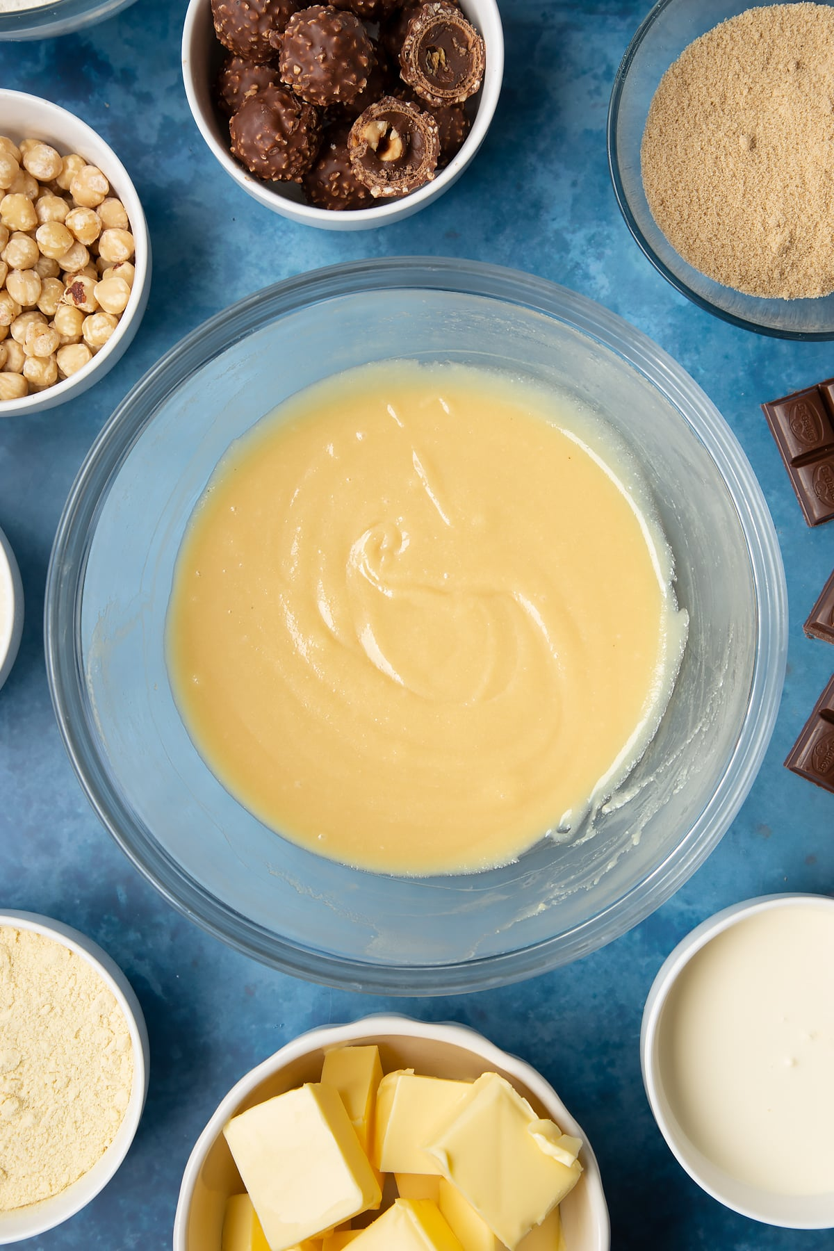 Smooth caramel in a glass mixing bowl. Ingredients to make a Ferrero Rocher slice surround the bowl.