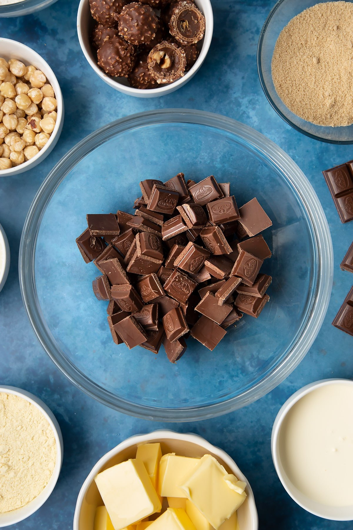 Dark chocolate in a glass mixing bowl. Ingredients to make a Ferrero Rocher slice surround the bowl.