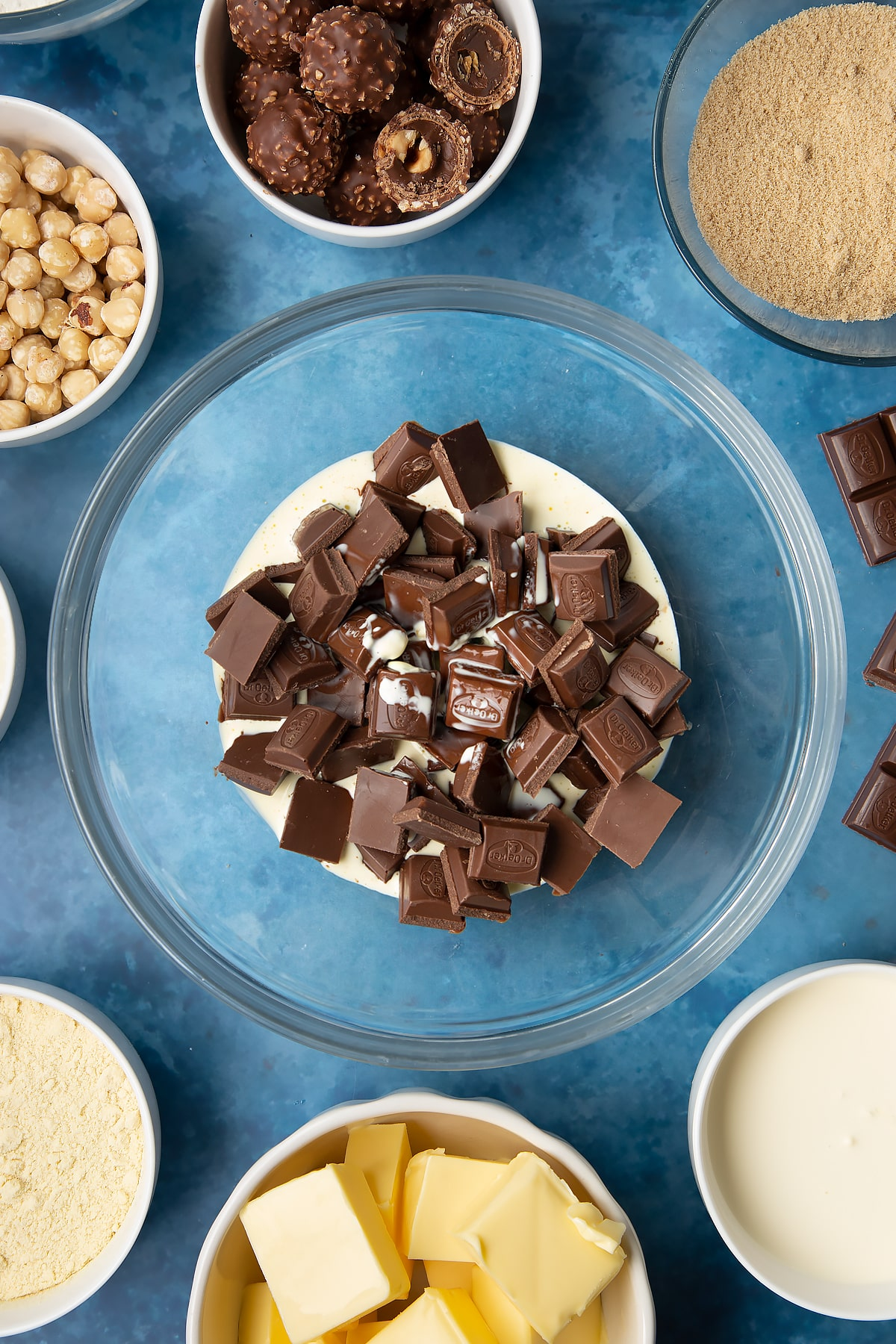 Dark chocolate and hot double cream in a glass mixing bowl. Ingredients to make a Ferrero Rocher slice surround the bowl.