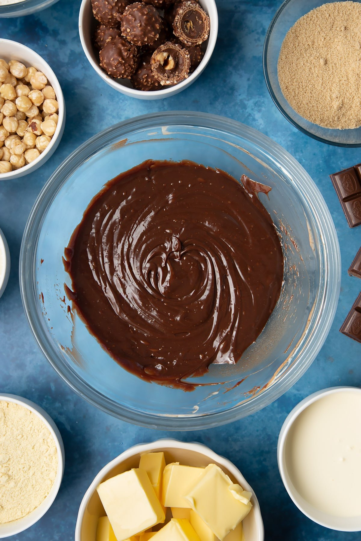 Dark chocolate ganache in a glass mixing bowl. Ingredients to make a Ferrero Rocher slice surround the bowl.