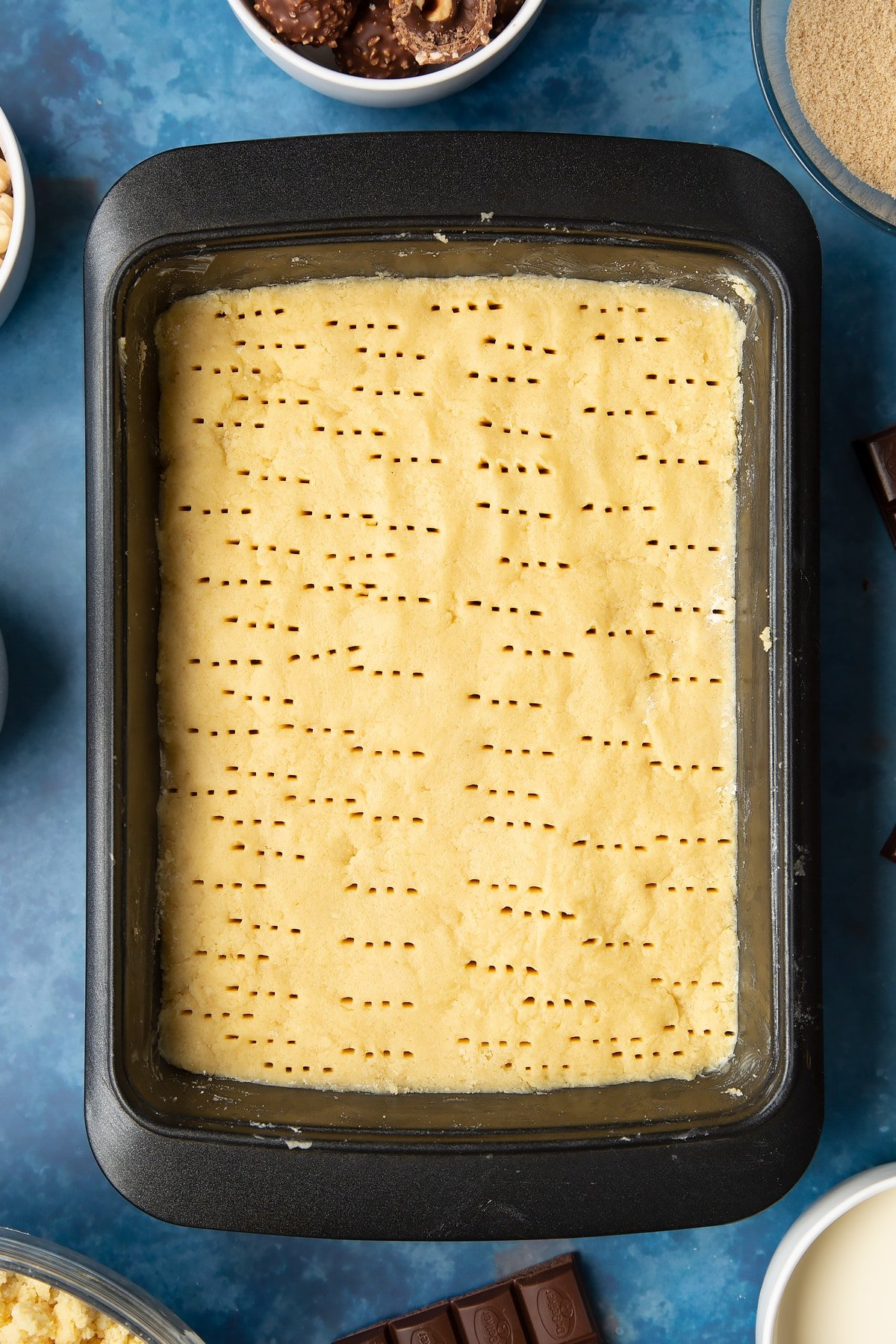 Shortbread dough pressed into a greased tray and pricked with a fork. Ingredients to make a Ferrero Rocher slice surround the tray.