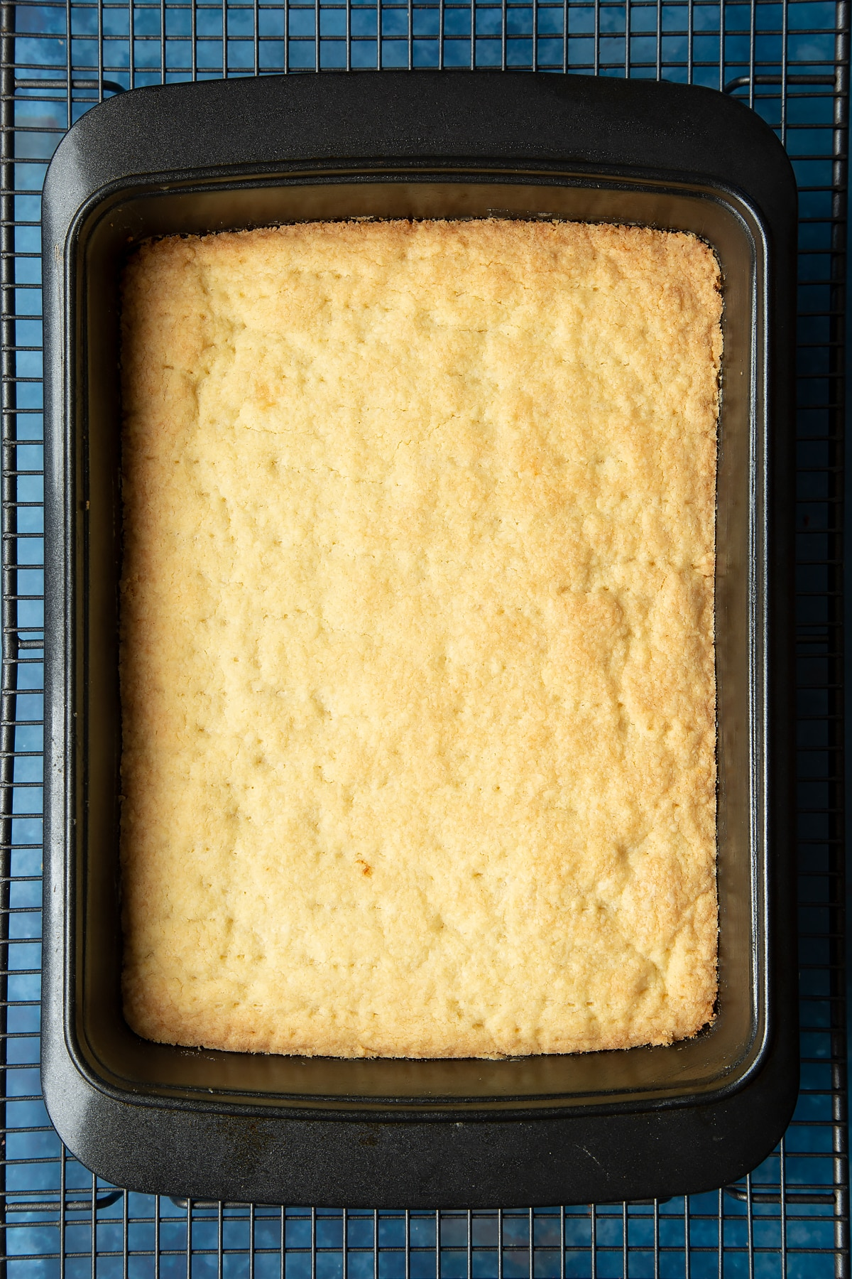 Cooked shortbread in a tray on a cooling rack.