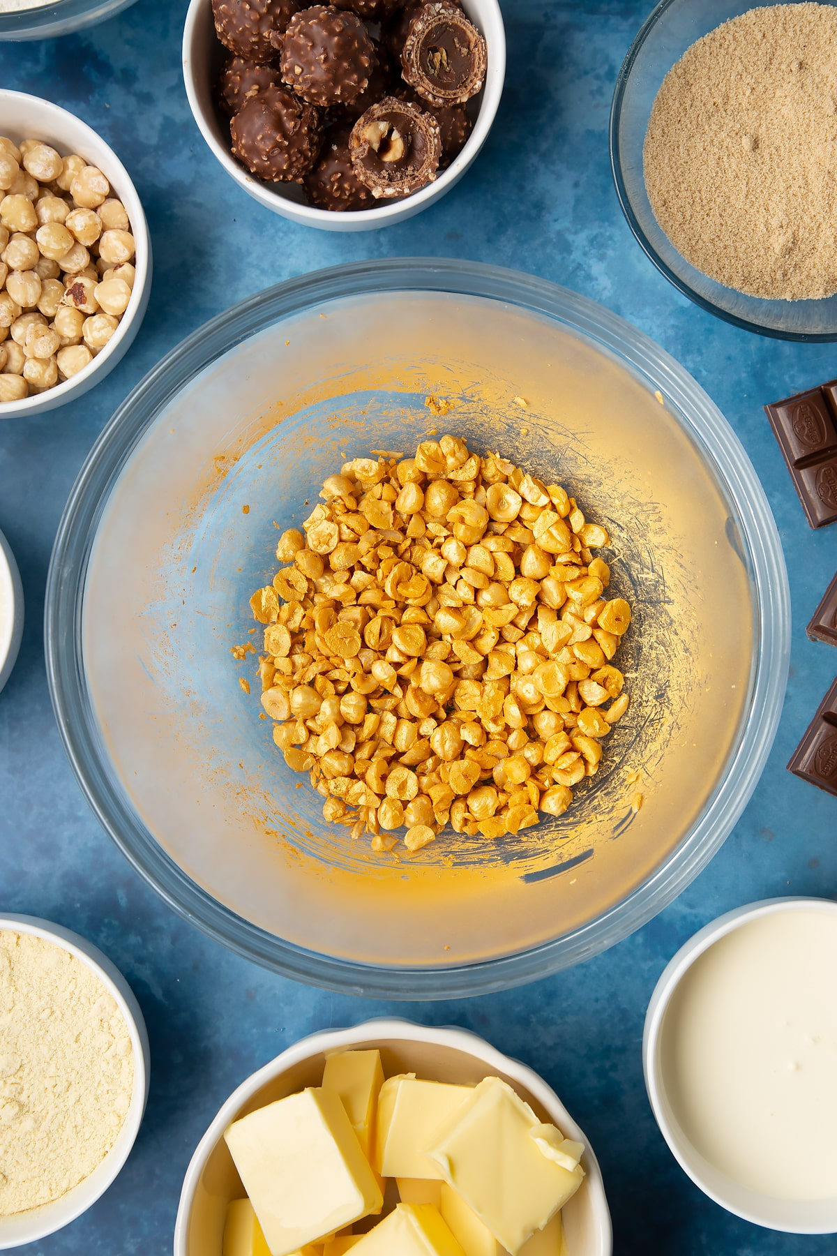 Chopped hazelnuts sprayed gold in a glass mixing bowl. Ingredients to make a Ferrero Rocher slice surround the bowl.