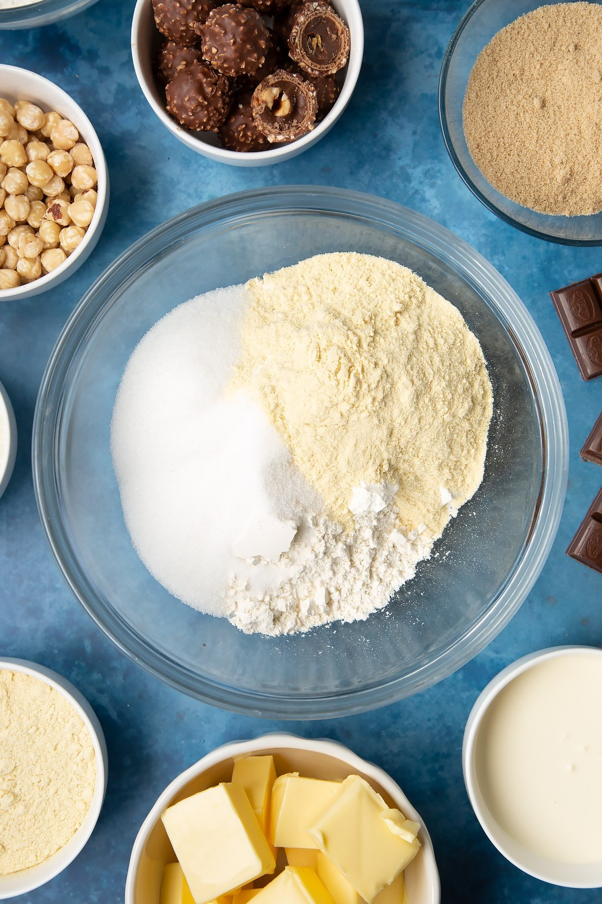 Flour, sugar and semolina in a glass mixing bowl. Ingredients to make a Ferrero Rocher slice surround the bowl.