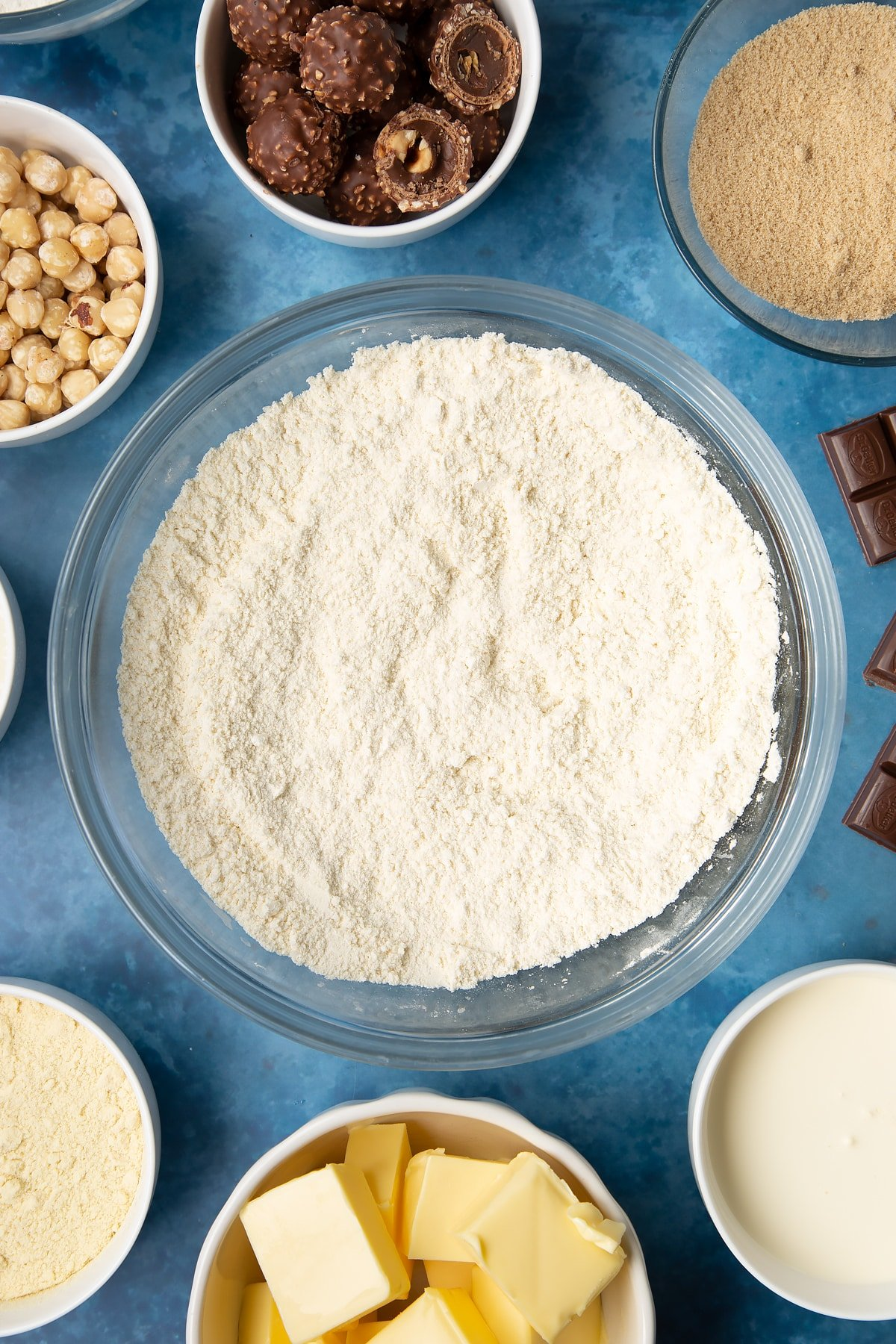 Flour, sugar and semolina mixed together in a glass mixing bowl. Ingredients to make a Ferrero Rocher slice surround the bowl.