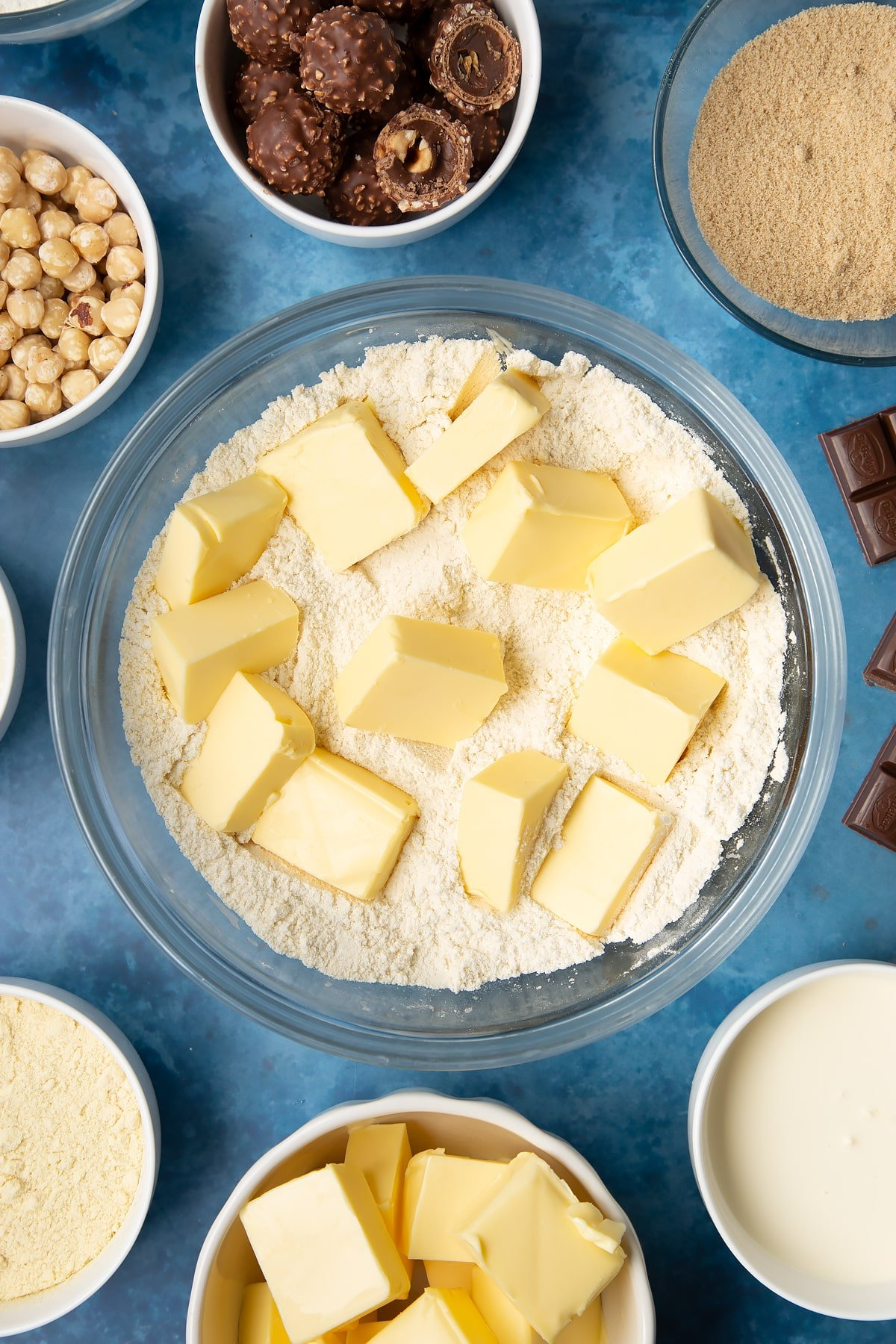 Flour, sugar, semolina and butter in a glass mixing bowl. Ingredients to make a Ferrero Rocher slice surround the bowl.