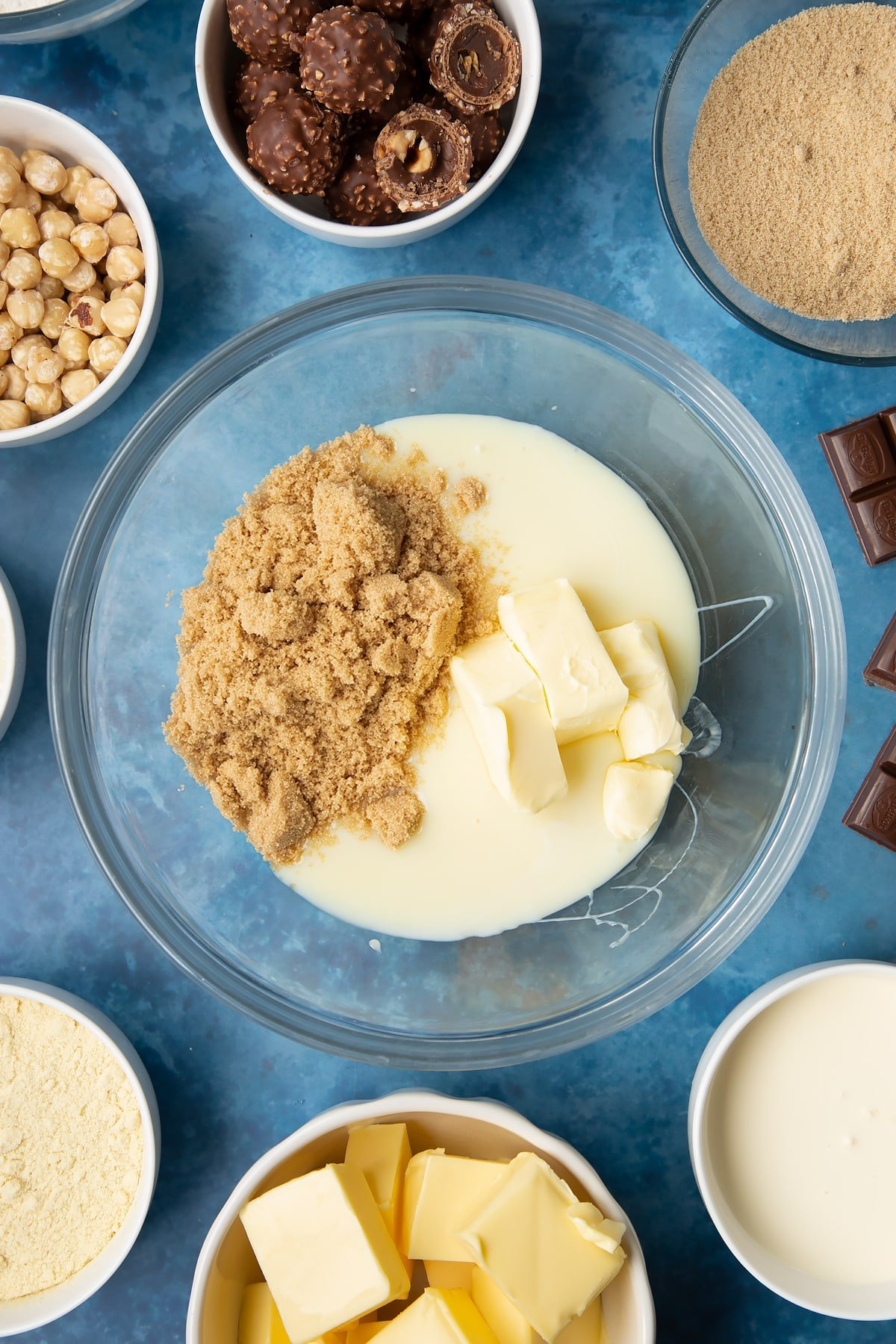 Brown sugar, butter and condensed milk in a glass mixing bowl. Ingredients to make a Ferrero Rocher slice surround the bowl.