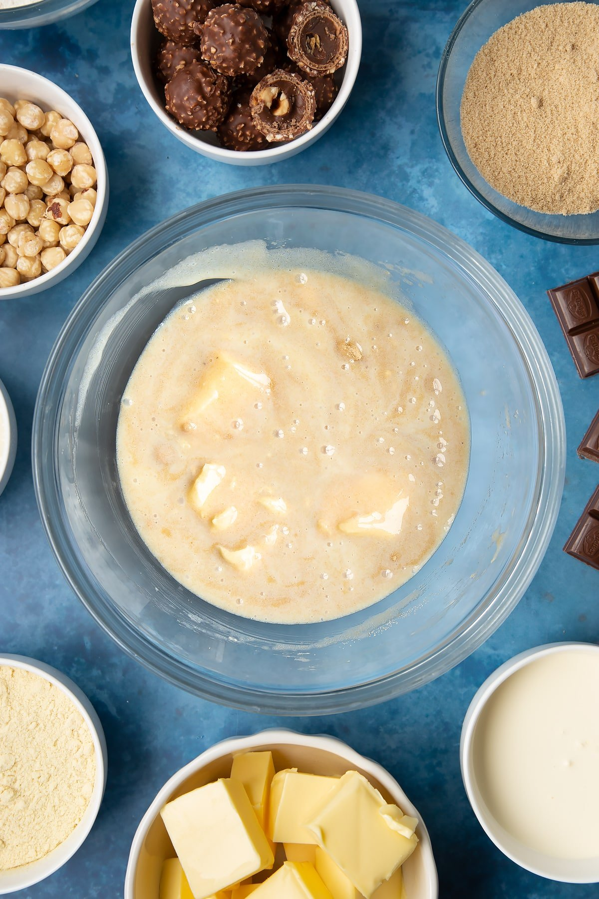 Brown sugar, butter and condensed milk stirred together in a glass mixing bowl. Ingredients to make a Ferrero Rocher slice surround the bowl.
