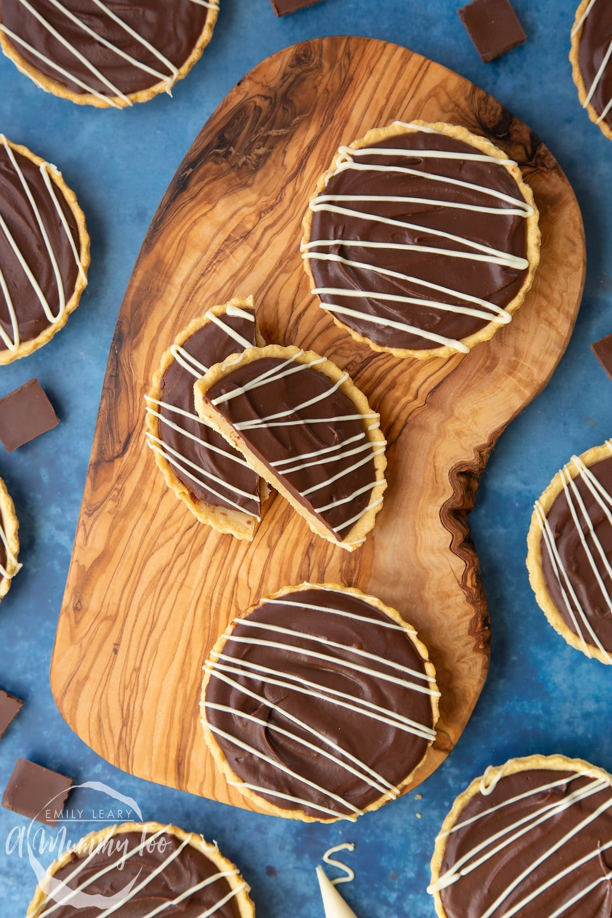 Mini chocolate tarts on an olive board. One tart has been cut in half.
