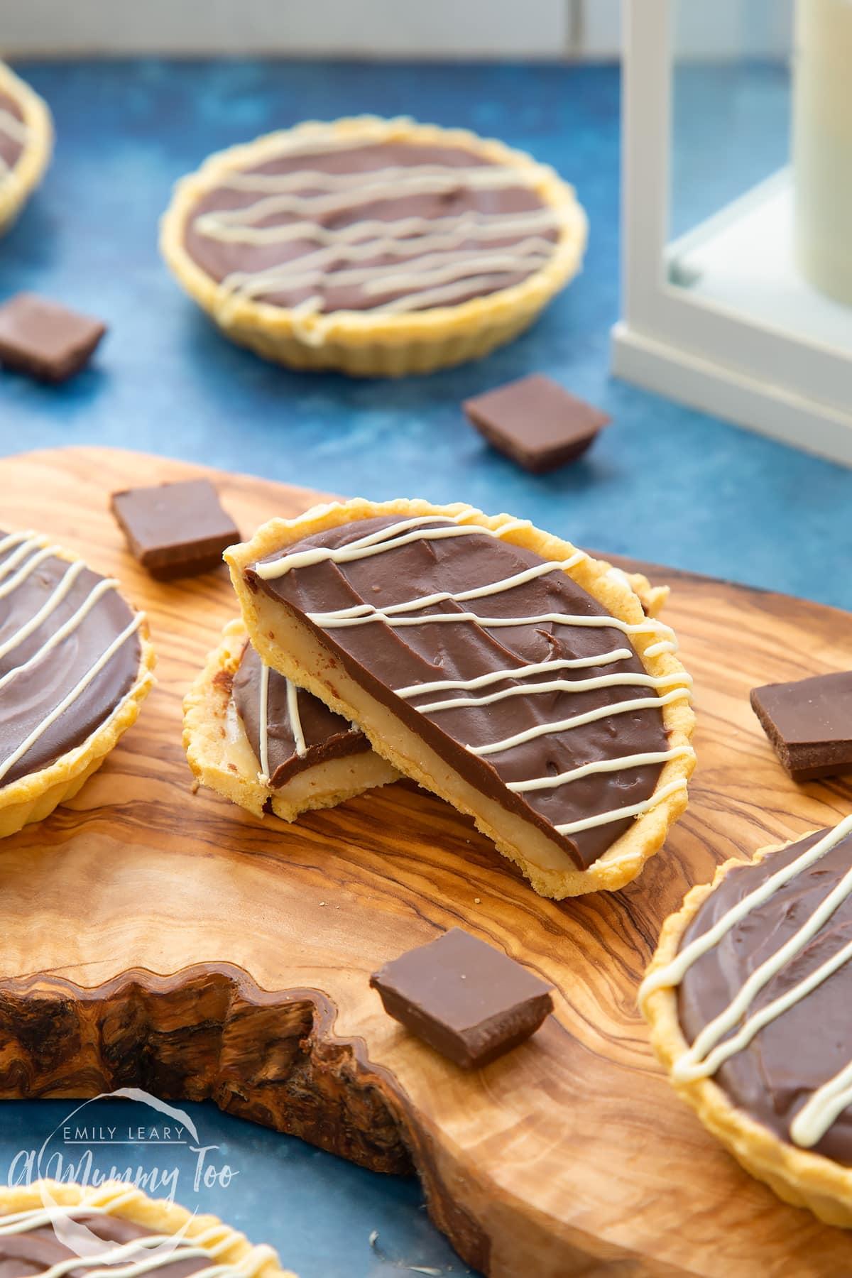 Mini chocolate tarts on an olive board. The tart in focus has been cut in half.