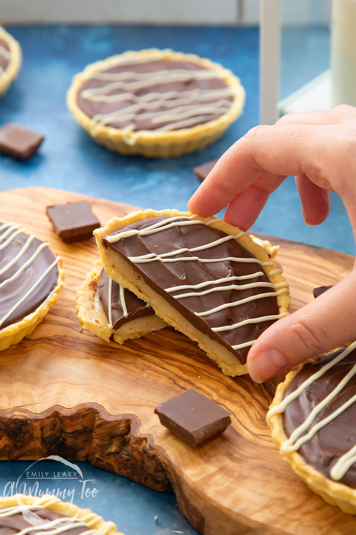 Mini chocolate tarts on an olive board. One tart has been cut in half. A hand holds a piece.