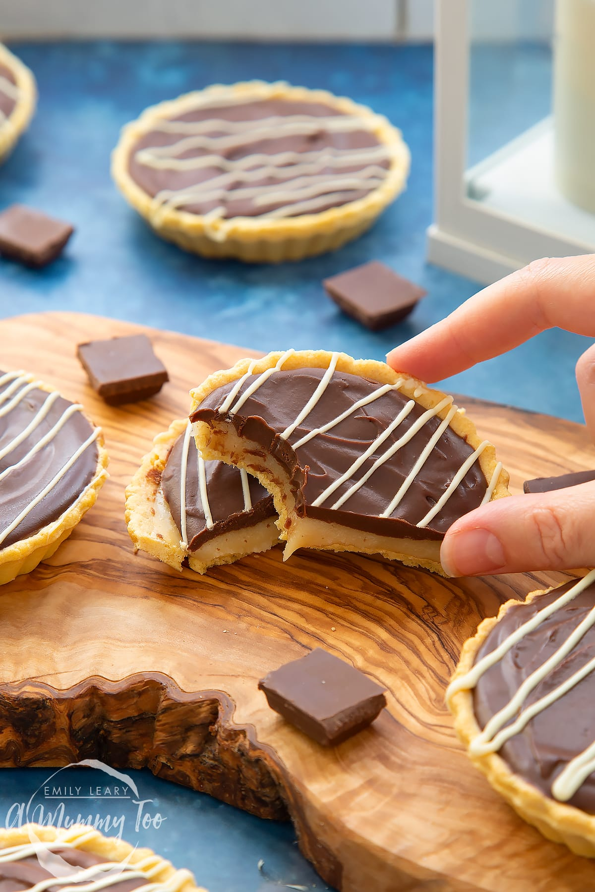 Mini chocolate tarts on an olive board. One tart has been cut in half. A hand holds a half, which has a bite out of it.