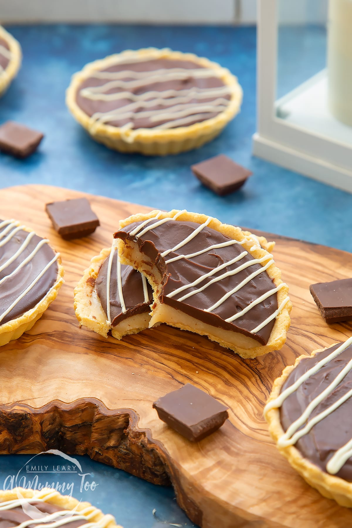 Mini chocolate tarts on an olive board. One tart has been cut in half. Once half has a bite out of it.